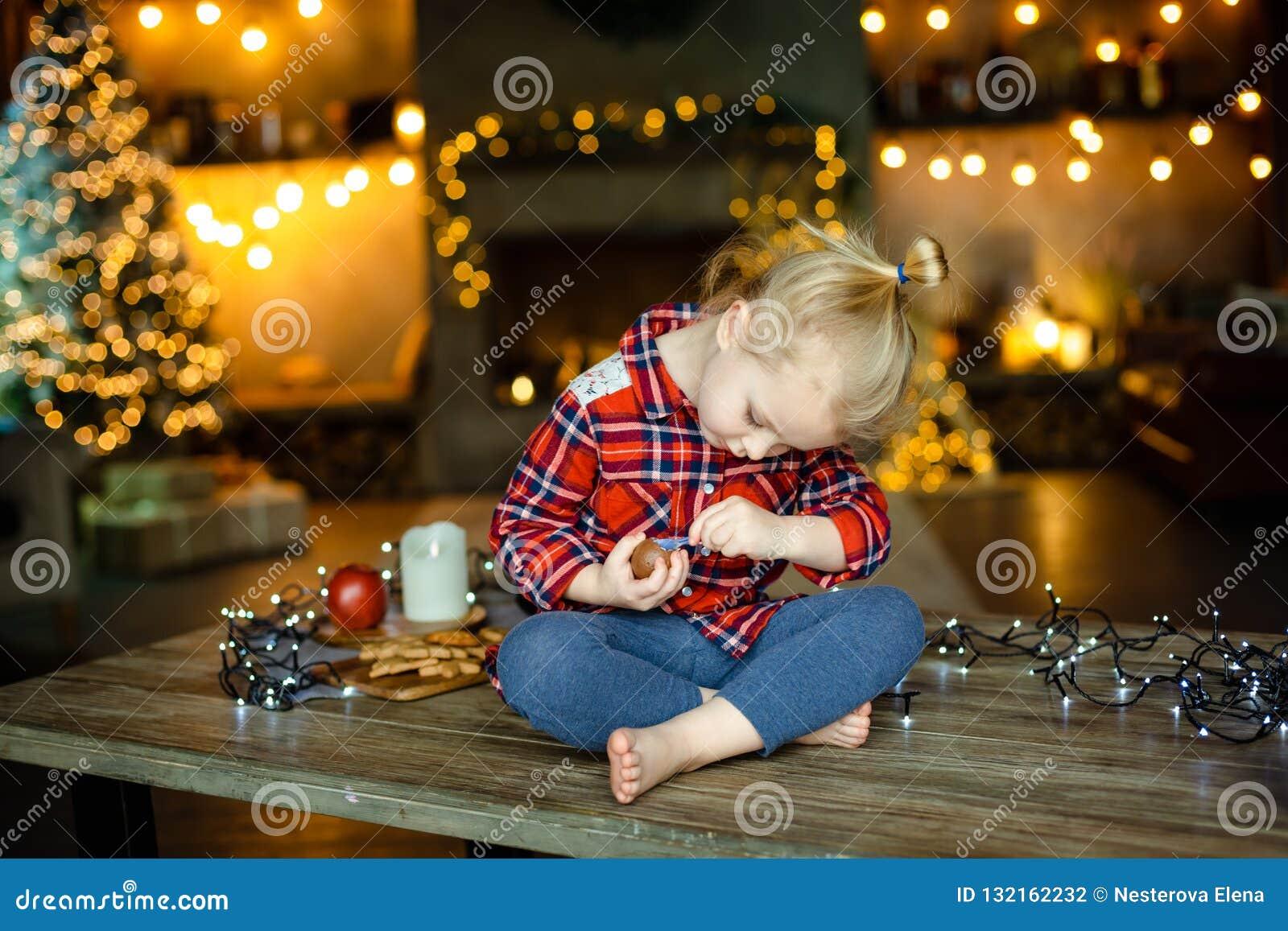 Pequeña muchacha rubia blanca que se sienta en una tabla de madera en la sala de estar del chalet, adornada para el ingenio del á