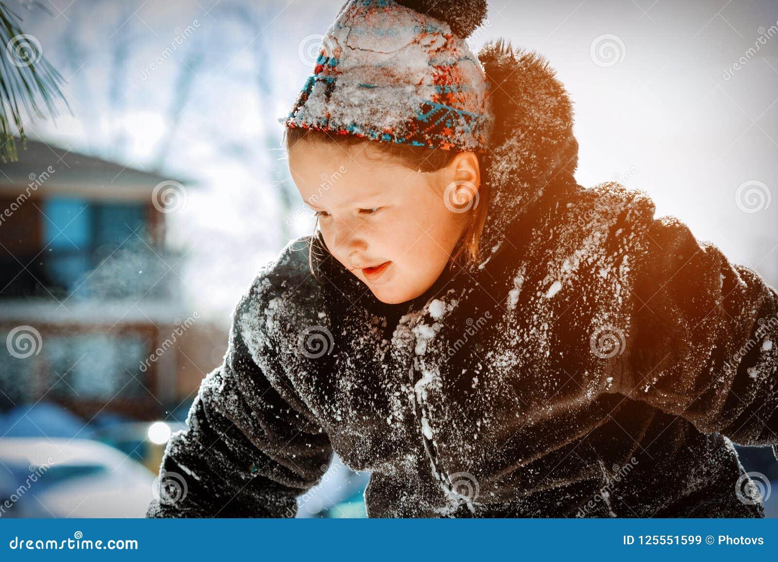 Pequeña muchacha sonriente feliz al aire libre en la nieve en ropa del invierno