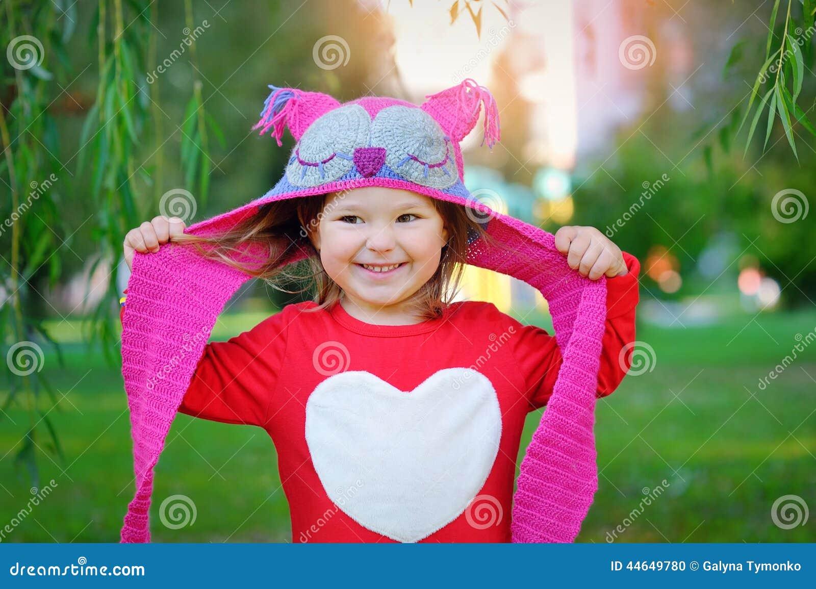 Pequeña niña pequeña de risa hermosa en una capa roja