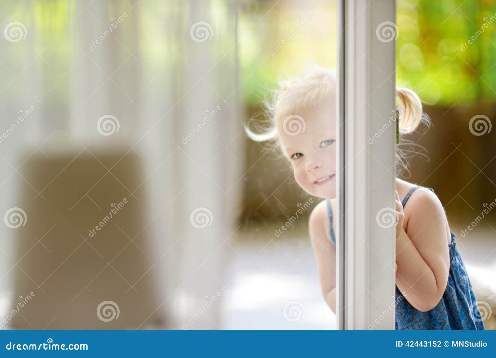 Pequeña niña pequeña linda que mira a escondidas en una ventana
