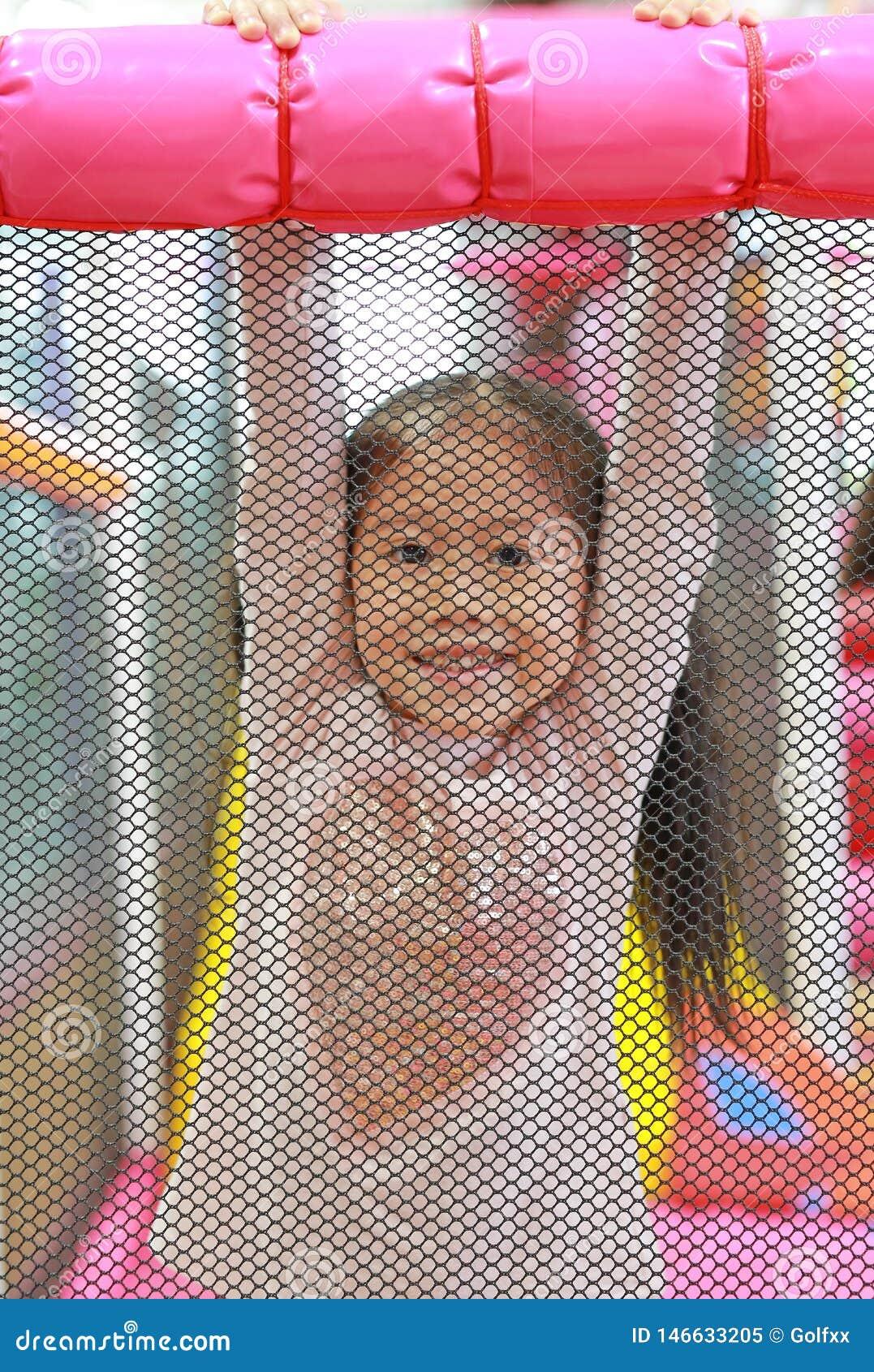 Pequeña parte posterior asiática de la muchacha del niño una red que juega y que cuelga en dentro patio Muchacha activa que se di