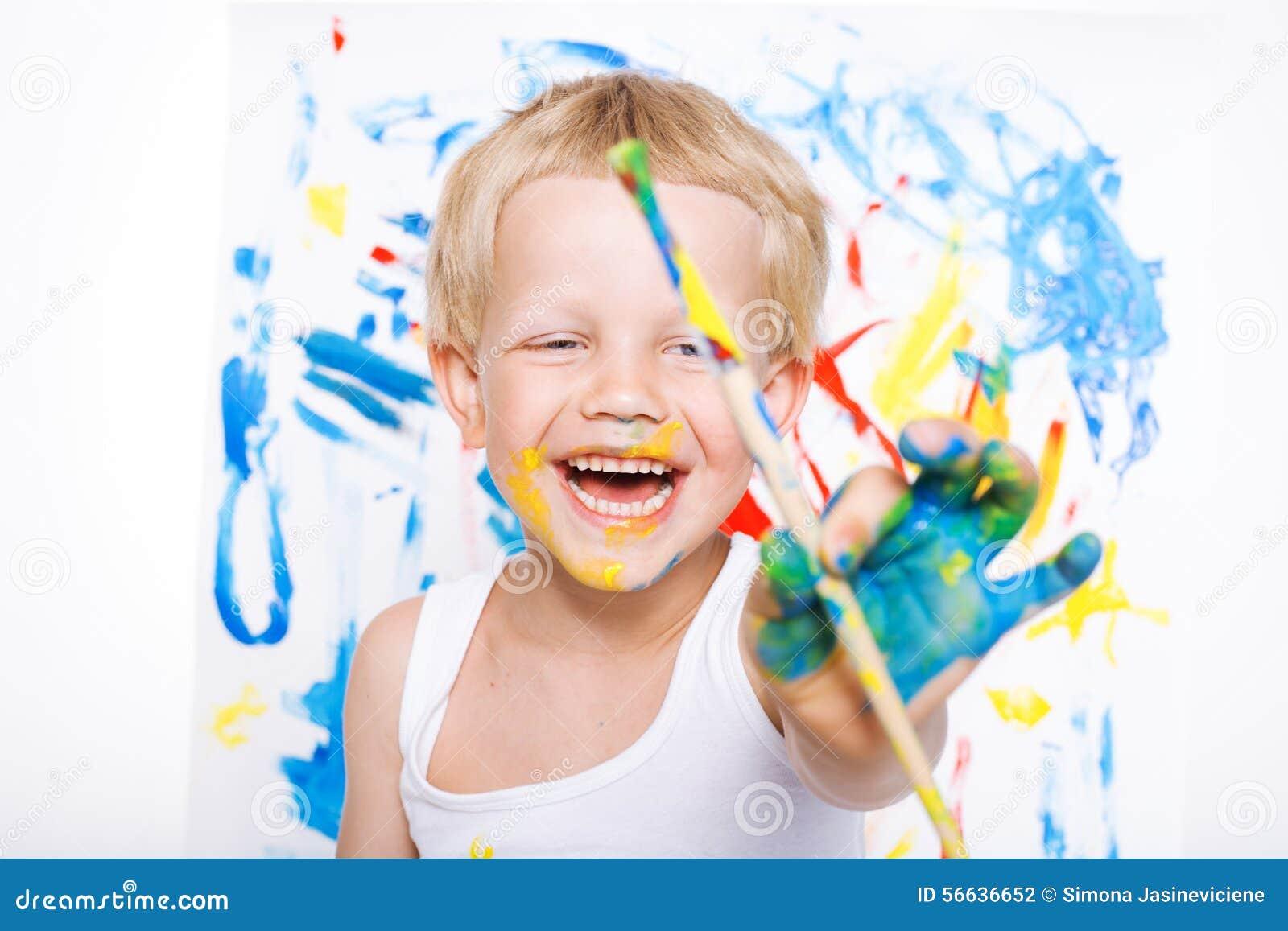 Pequeña pintura sucia del niño con la imagen de la brocha en el caballete Educación creatividad Escuela pre-entrenamiento Retrato