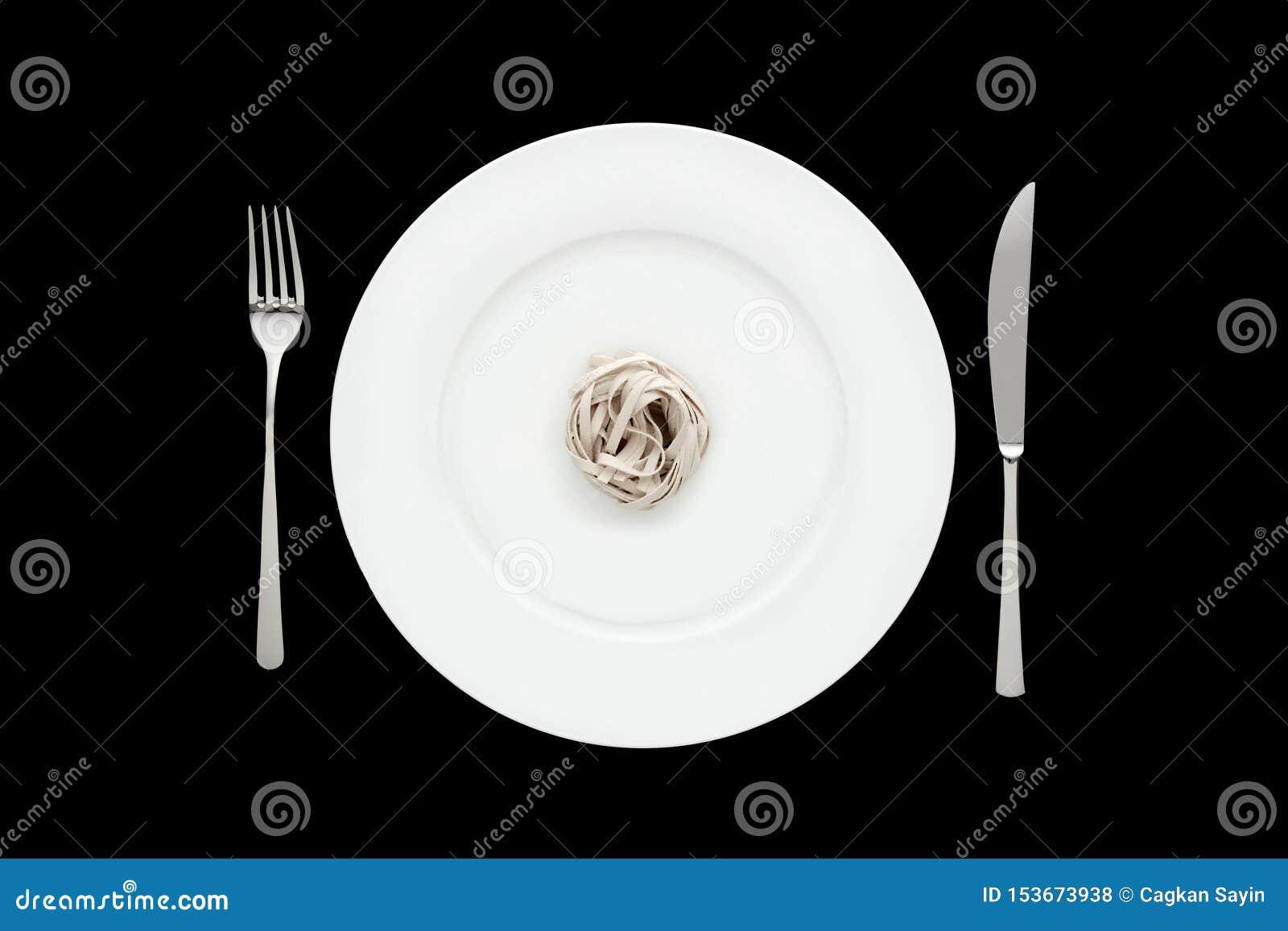 Pequeña porción de pastas de los tallarines en la placa blanca redonda con la bifurcación y el cuchillo en fondo negro aislado