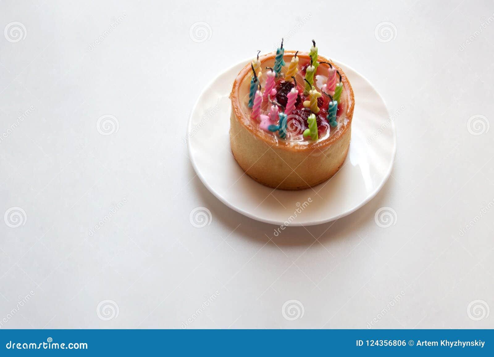 Pequeña torta de cumpleaños con las velas brillantes