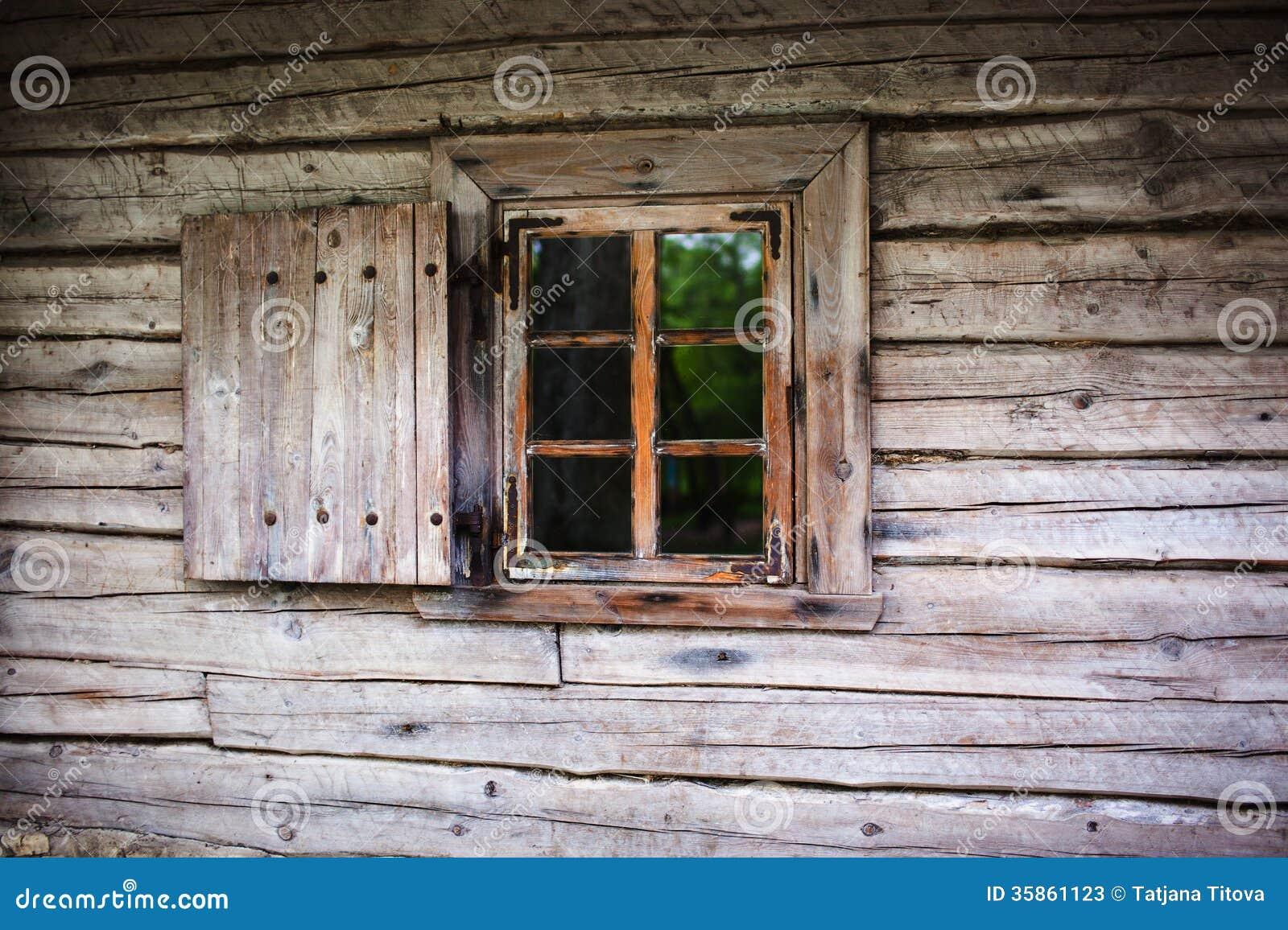 Pequeña ventana en la pared de una casa de madera vieja