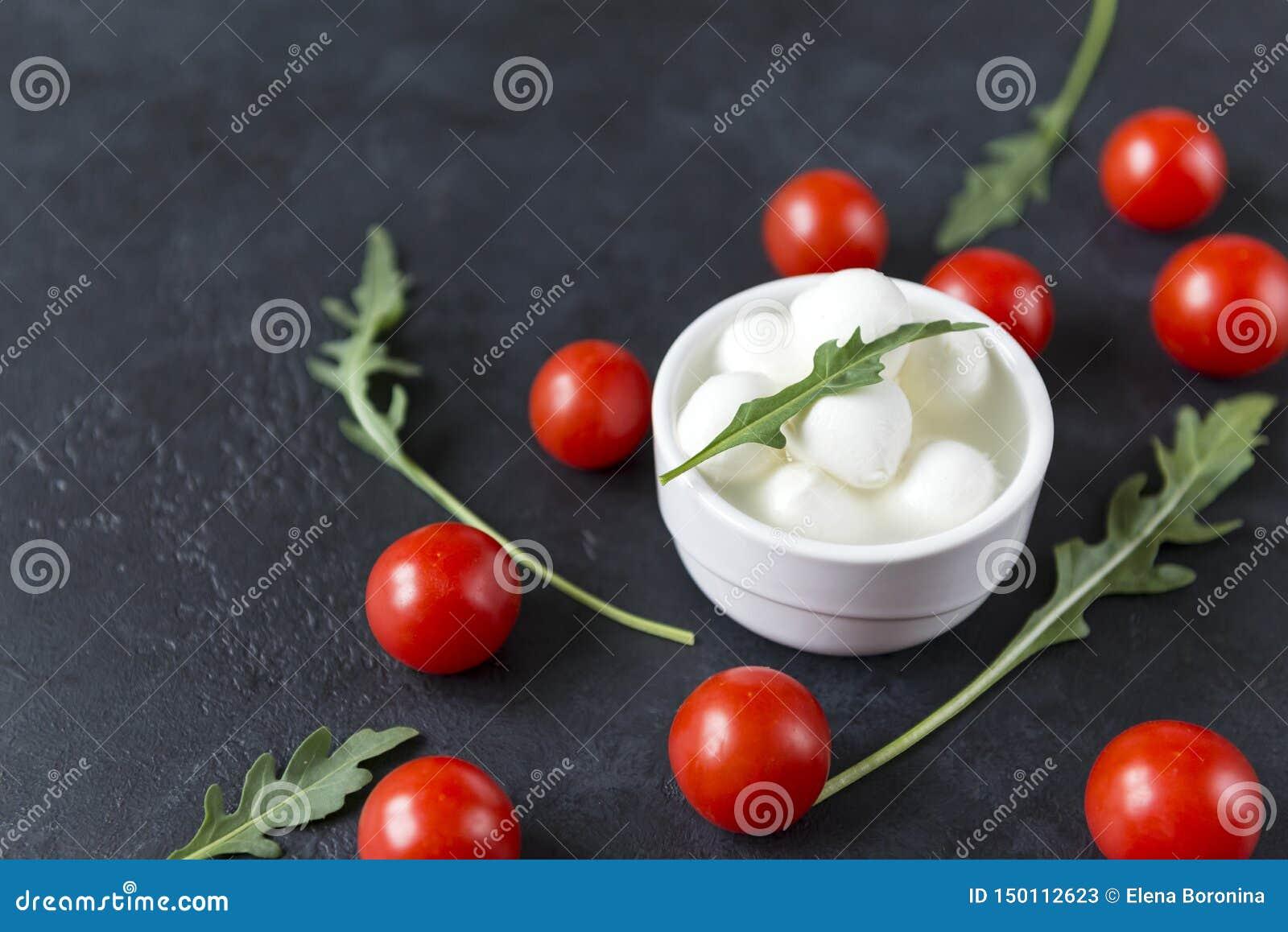 Pequeñas bolas de la mozzarella en un cuenco con arugula, tomates de cereza en un fondo negro