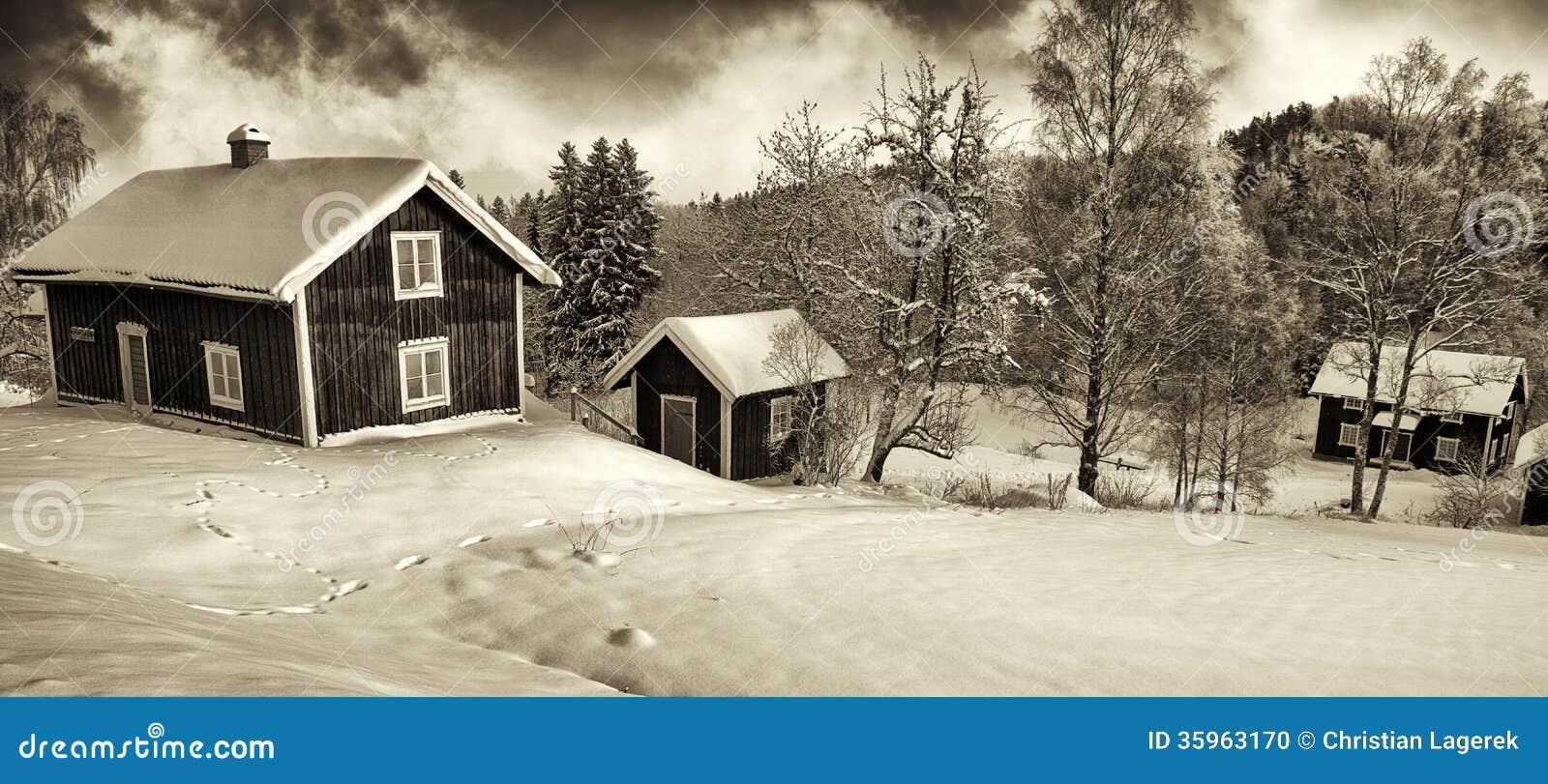 Pequeñas cabañas en viejo paisaje rural del invierno