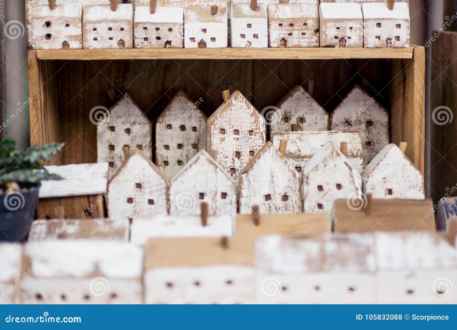 Peque as casas de madera hechas a mano en fila en estante for Decoracion de casas hechas a mano