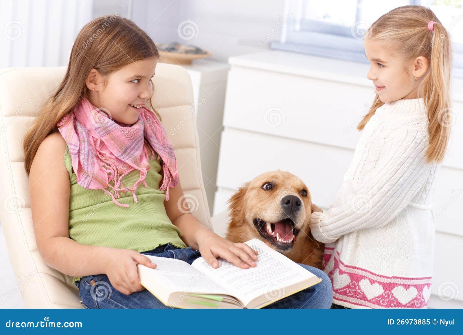Pequeñas hermanas con el perro de animal doméstico en el país