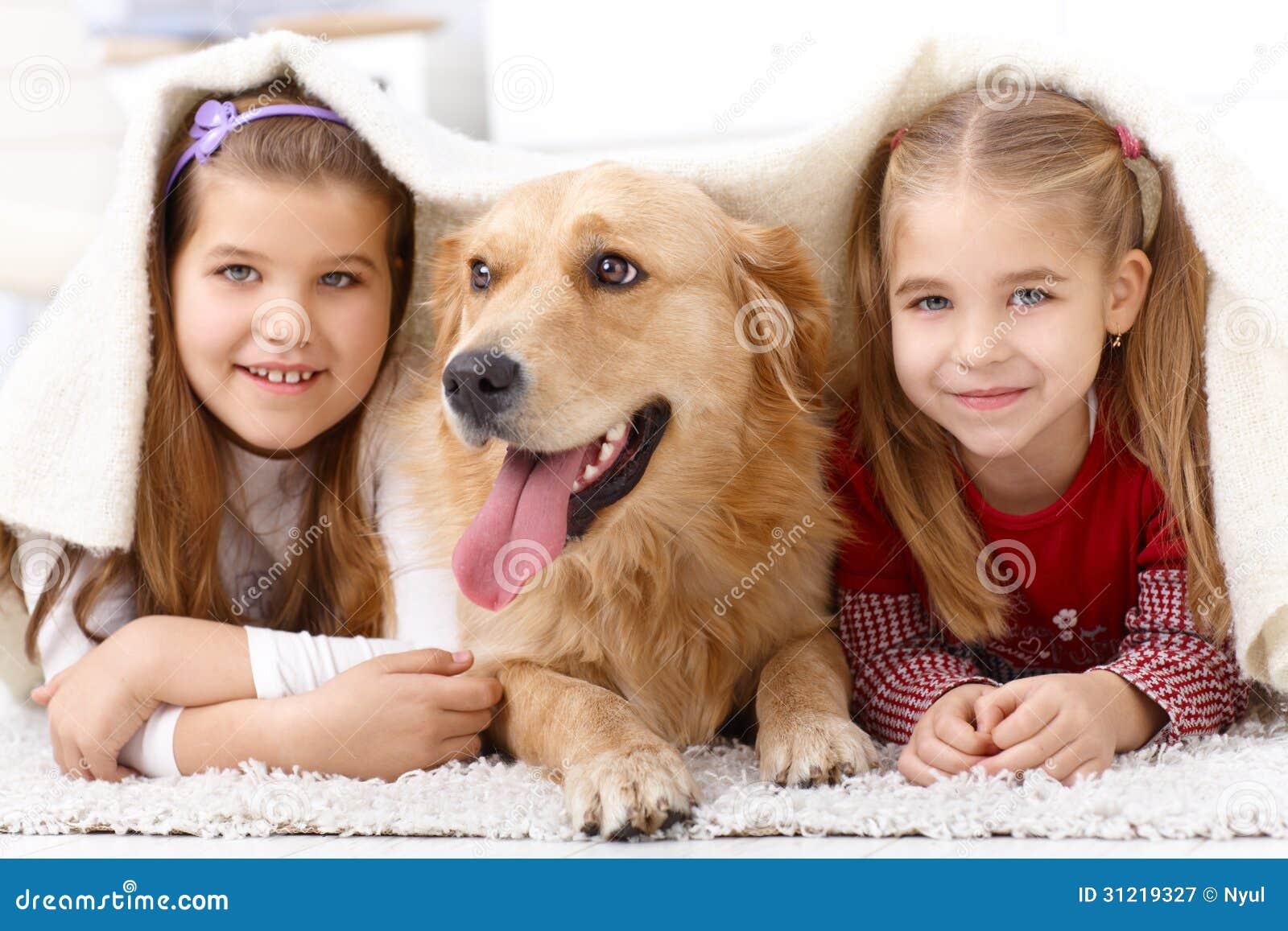 Pequeñas hermanas que se divierten con el perro casero