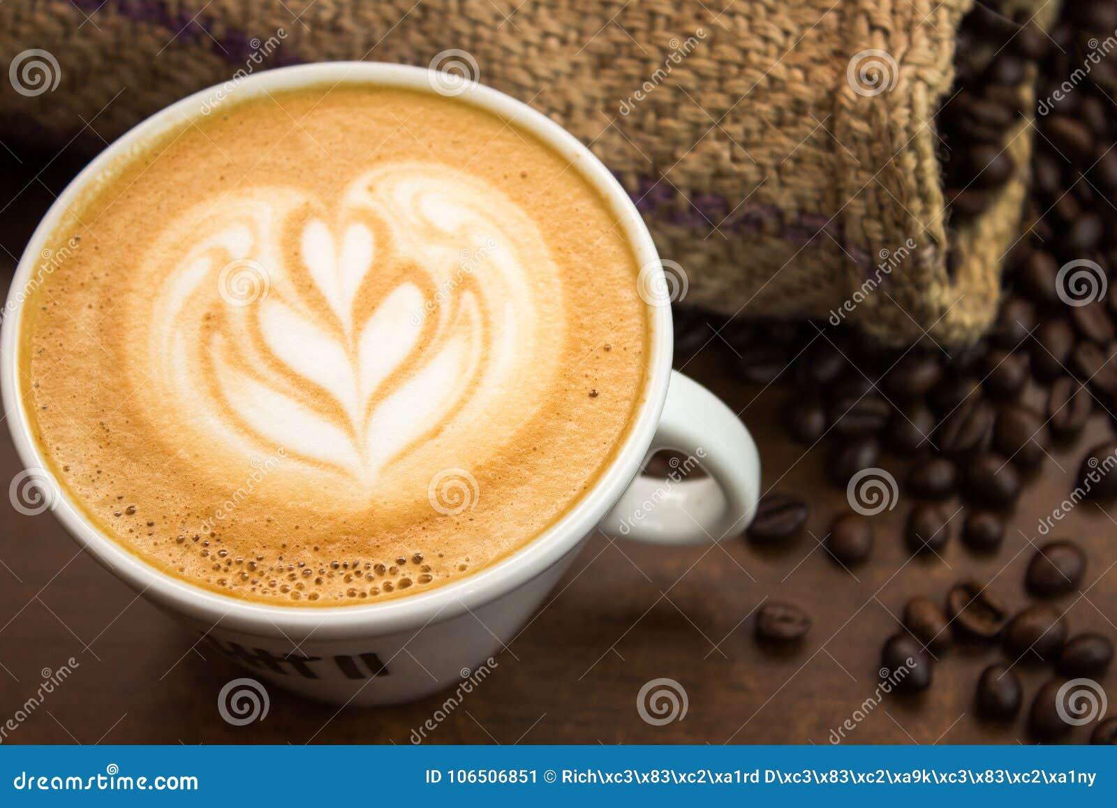 Pequeño arte del latte del tulipán con las habas y el saco del coffe