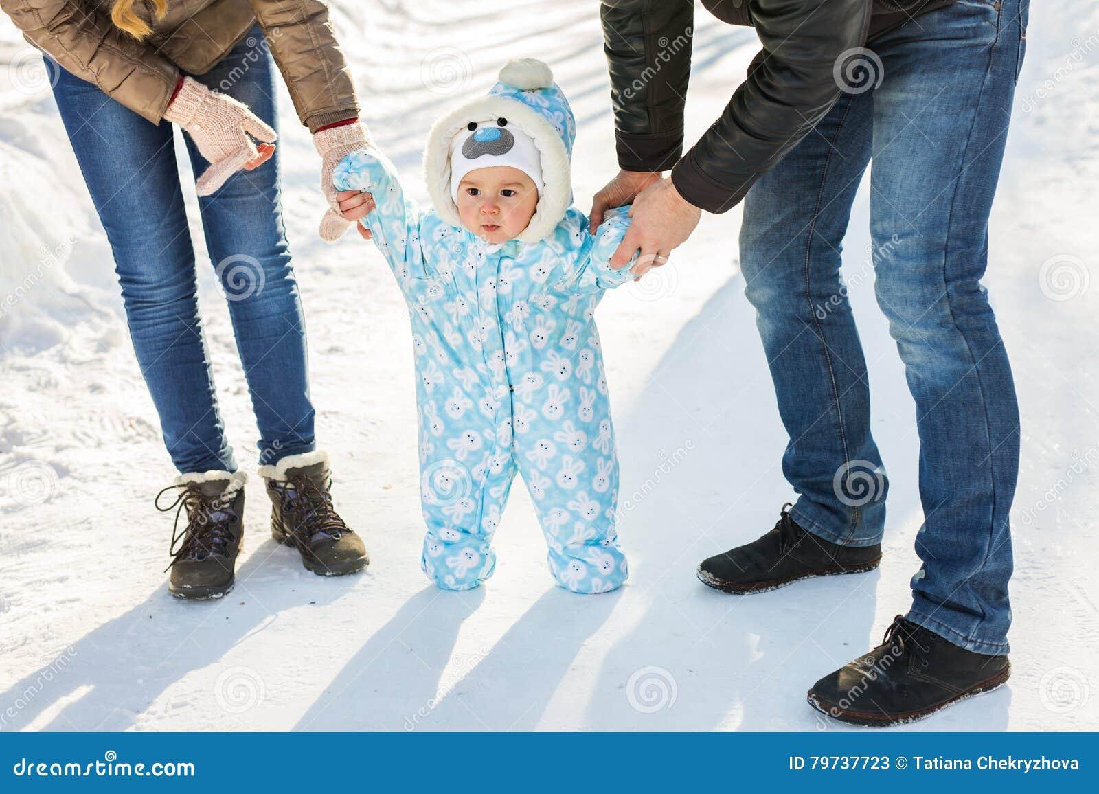 Pequeño bebé que aprende caminar La madre y el padre con el niño pequeño en el invierno parquean