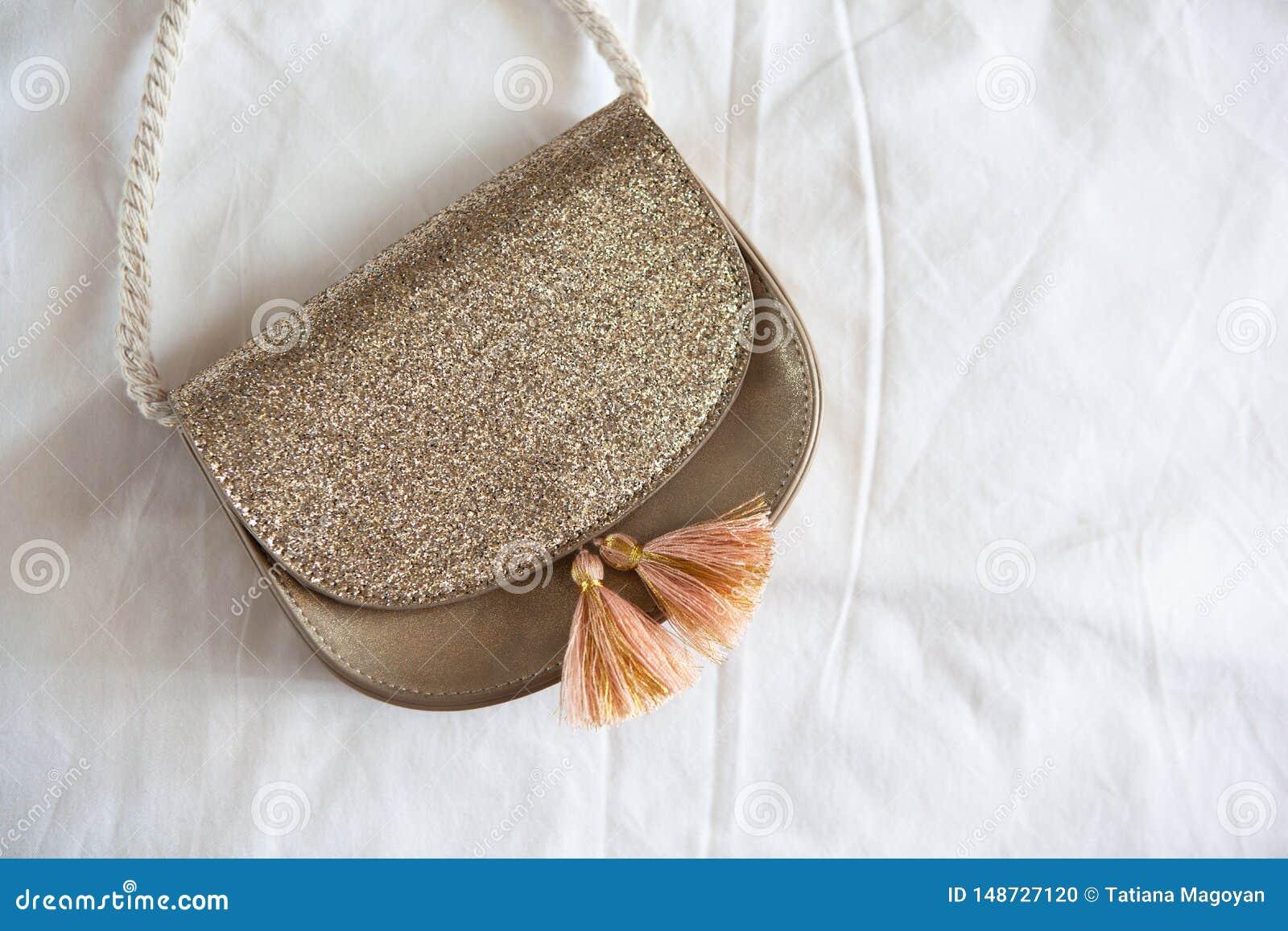 Peque?o bolso de oro de la silla de montar con las borlas y mentiras de la manija de la cuerda en la hoja blanca desgre?ada Tarif