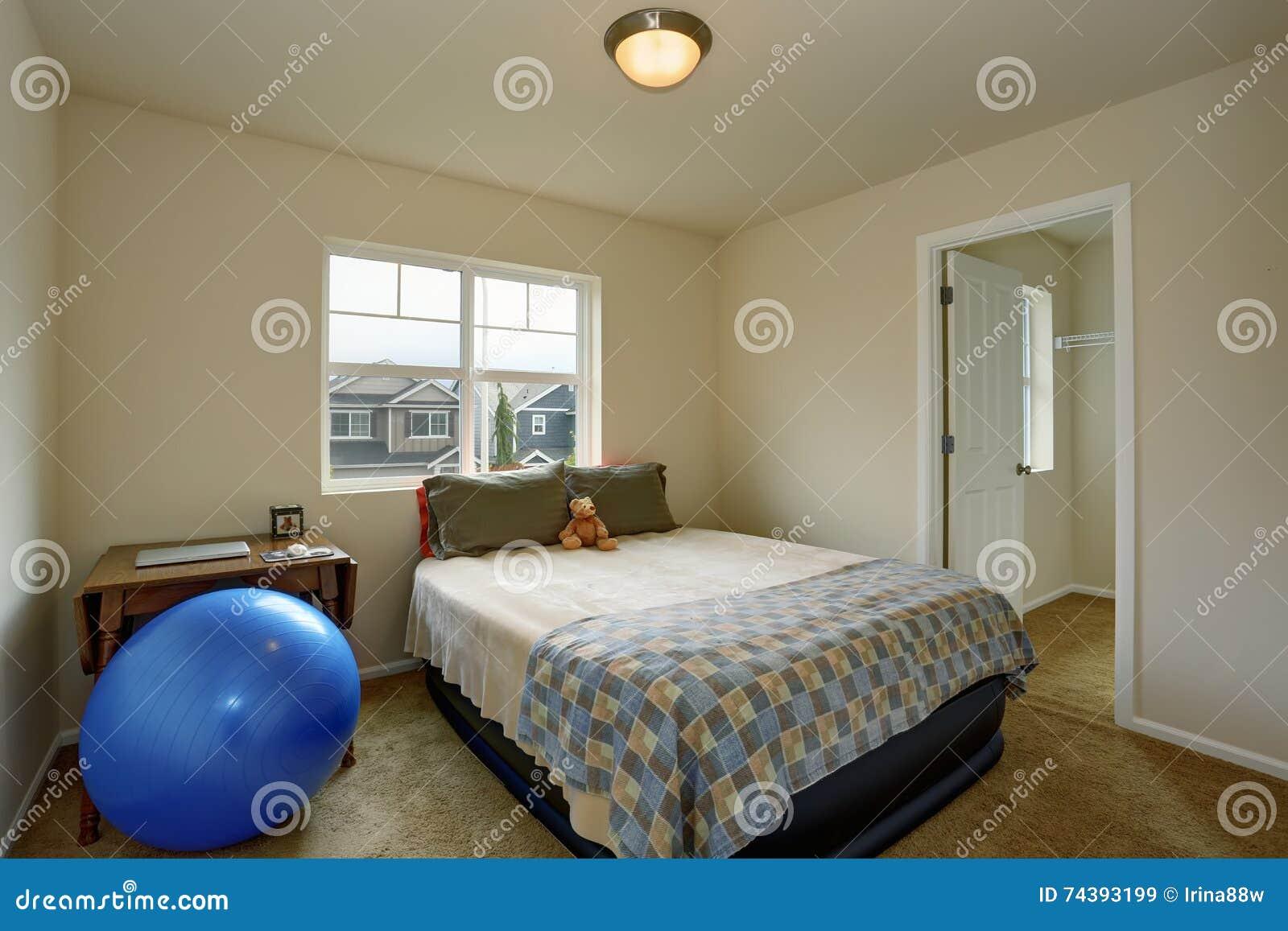Pequeño dormitorio de los niños con la tabla, la bola azul y la pequeña cama verde
