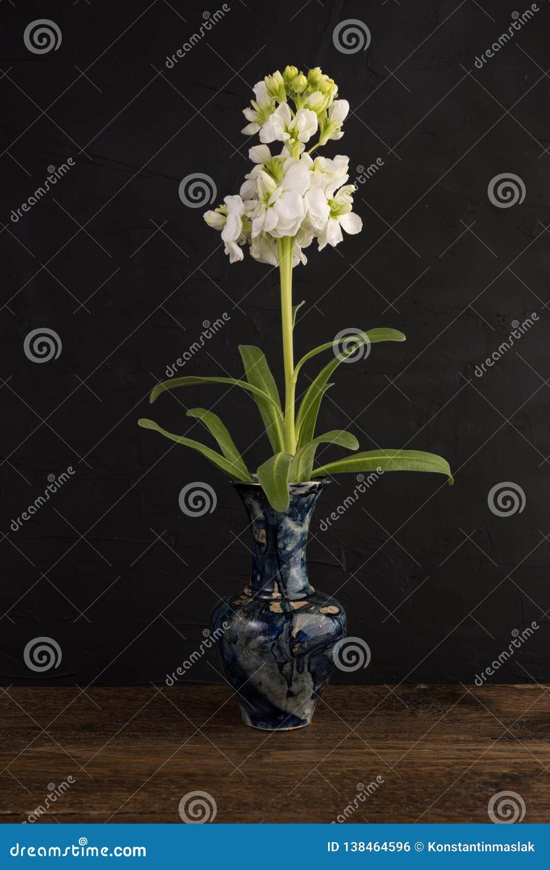 Pequeño florero de mármol con el manojo de flores blancas en negro