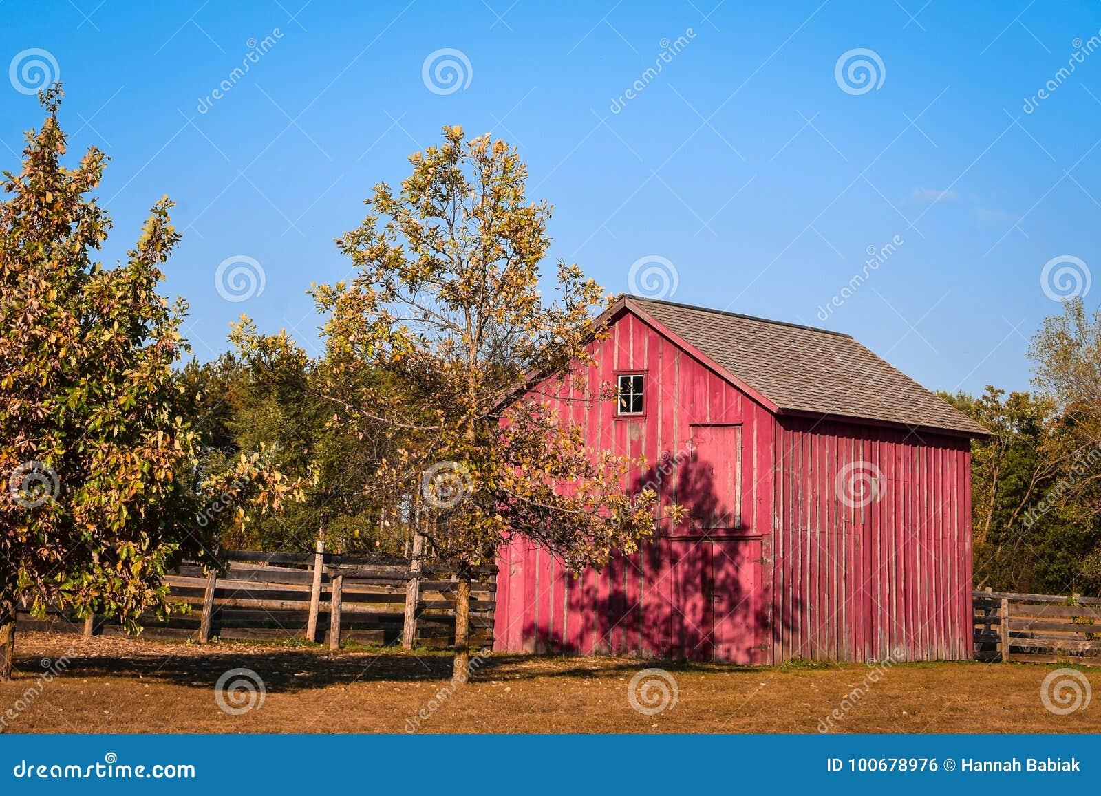 Pequeño granero rojo con la cerca