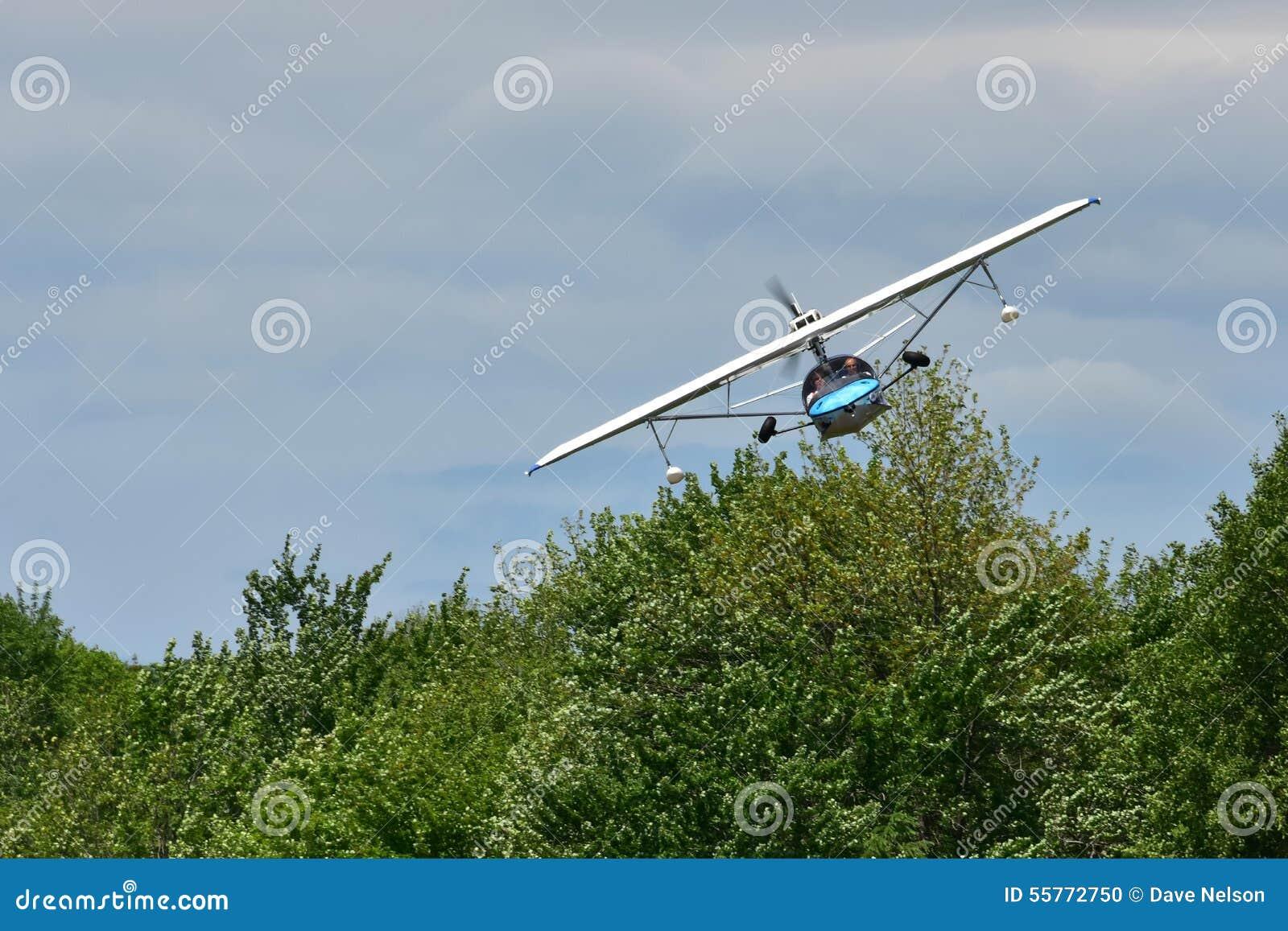 Pequeño hidroavión en vuelo bajo sobre los árboles 1