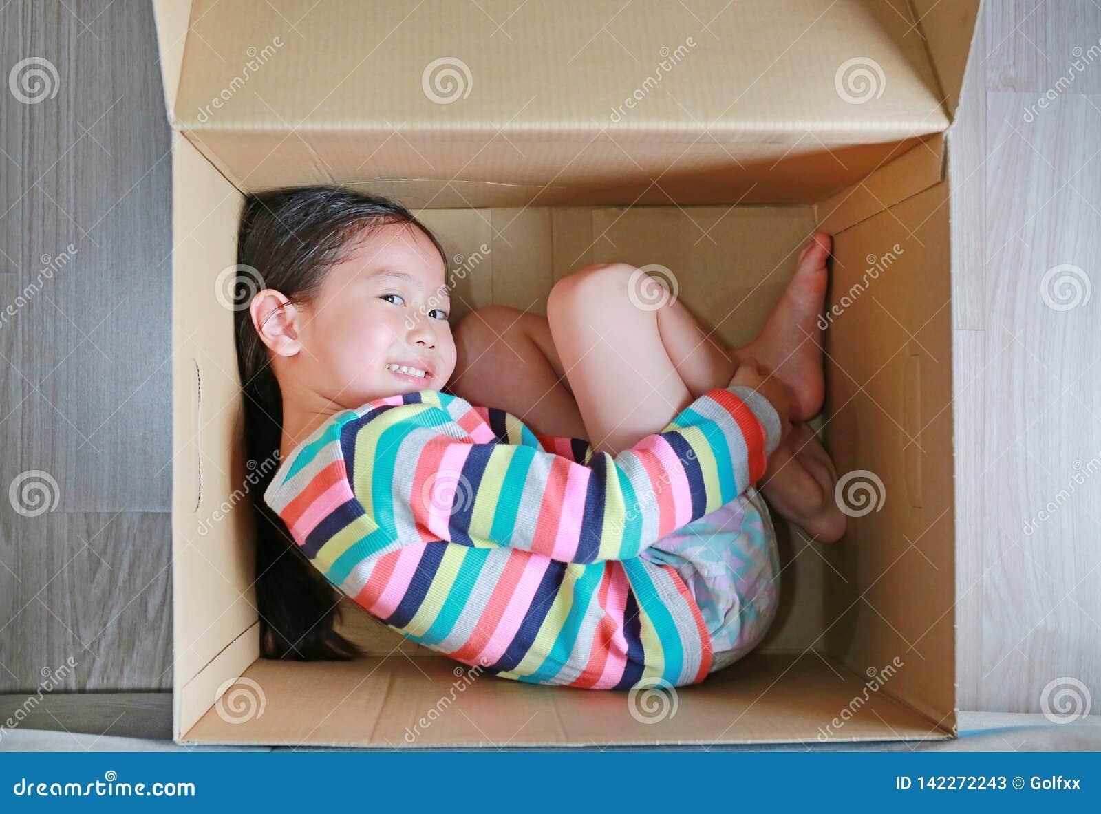 Pequeño juego asiático feliz de la muchacha del niño y mentira en caja de cartón grande