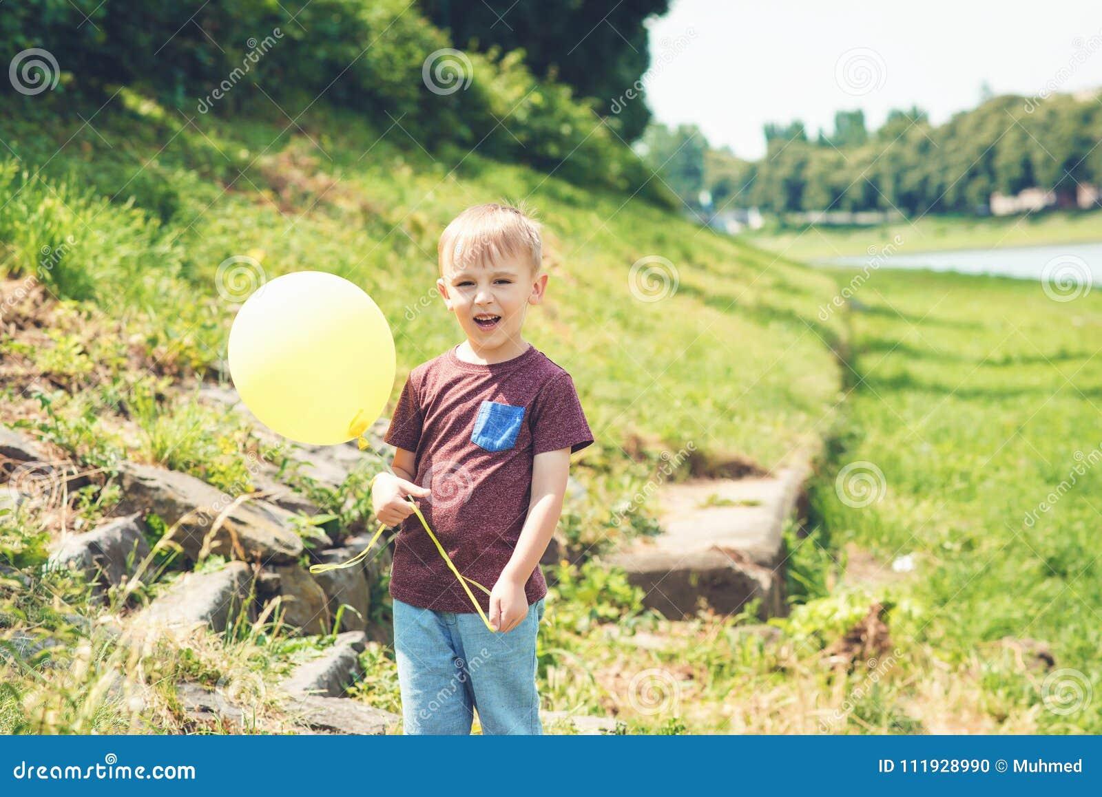 Pequeño juego divertido del muchacho con el globo amarillo al aire libre