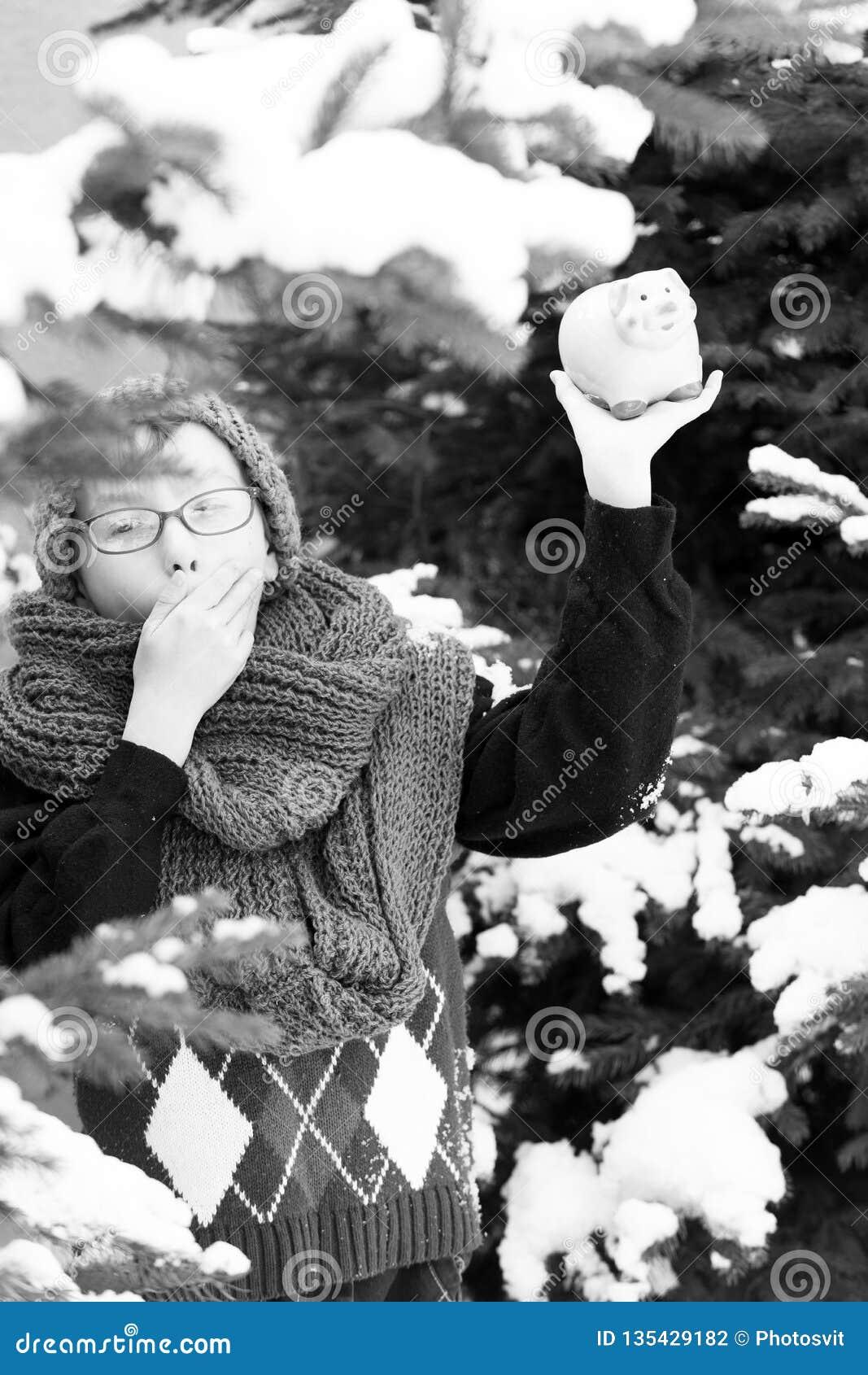 Pequeño muchacho con el moneybox en el invierno al aire libre
