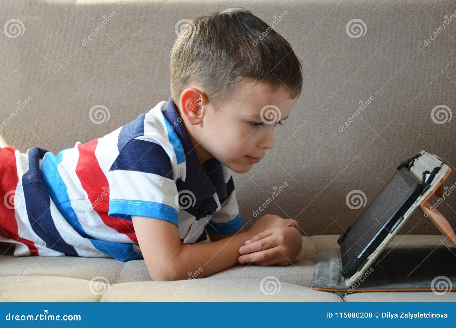 Pequeño muchacho lindo en una camiseta verde que juega a juegos en una tableta y que mira historietas Niño con la tableta