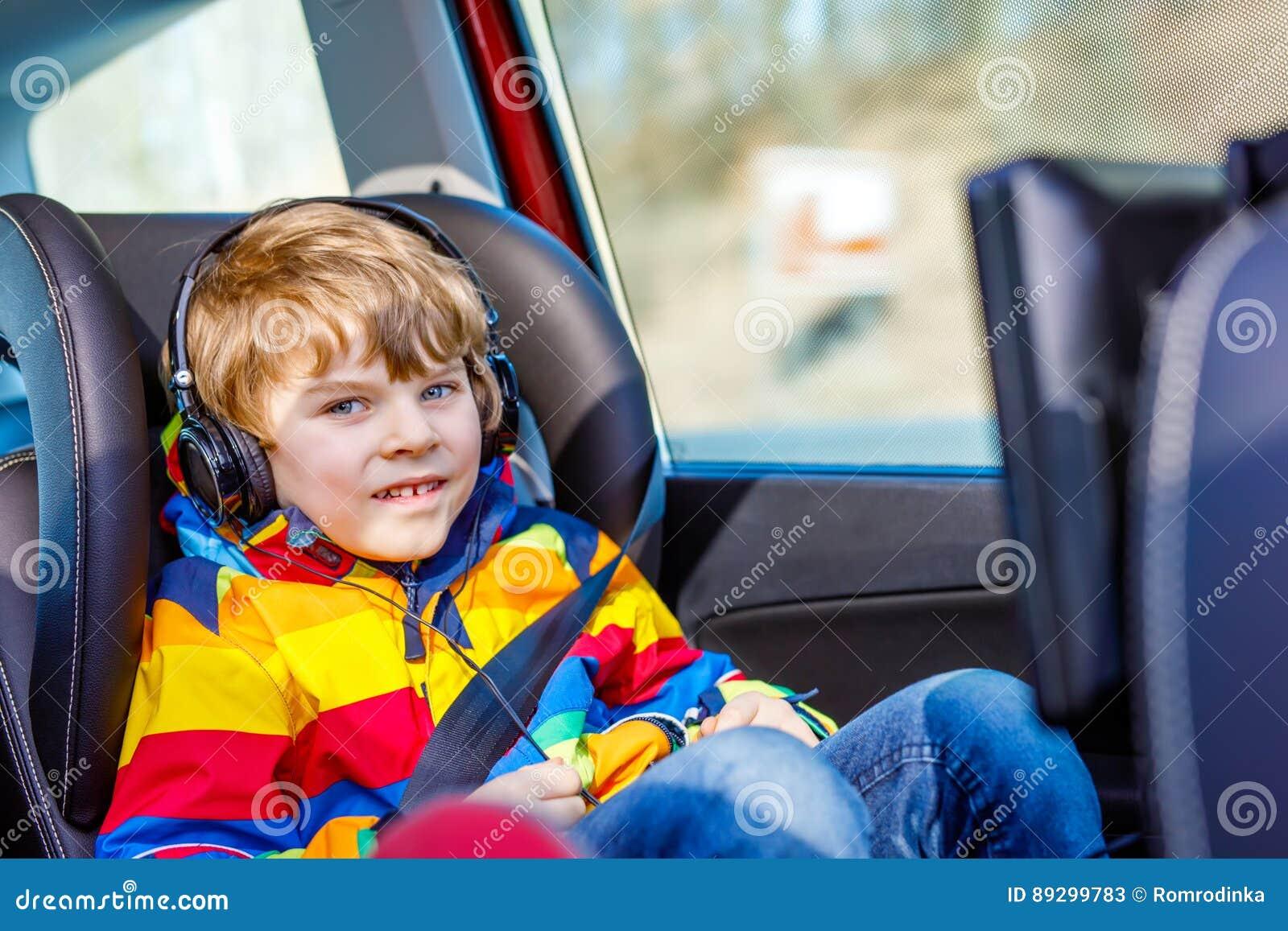 Pequeño muchacho rubio del niño que mira la TV o el DVD con los auriculares durante la impulsión larga del coche