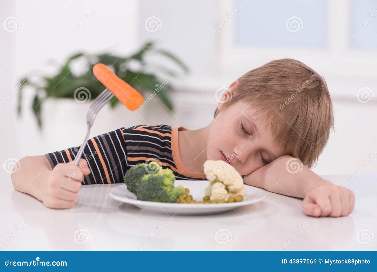 Pequeño muchacho rubio que come en la cocina
