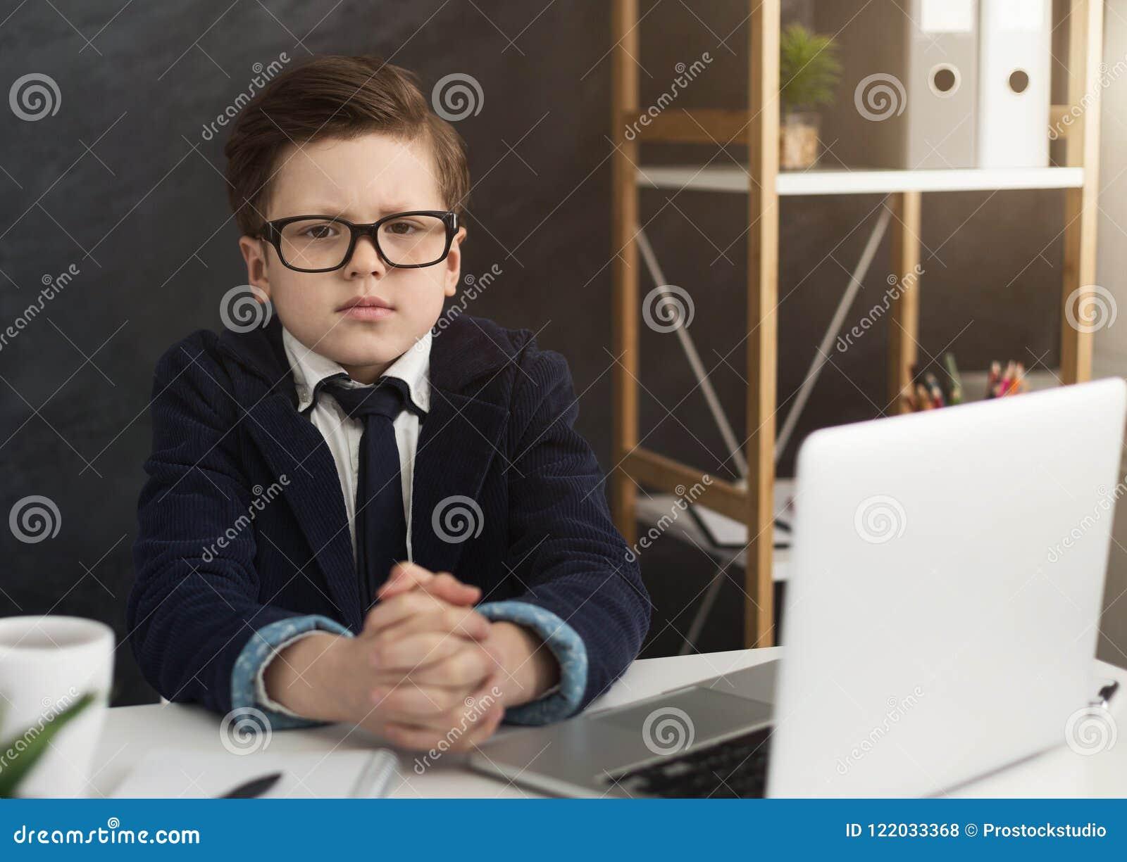 Pequeño muchacho serio que se sienta en la tabla de la oficina