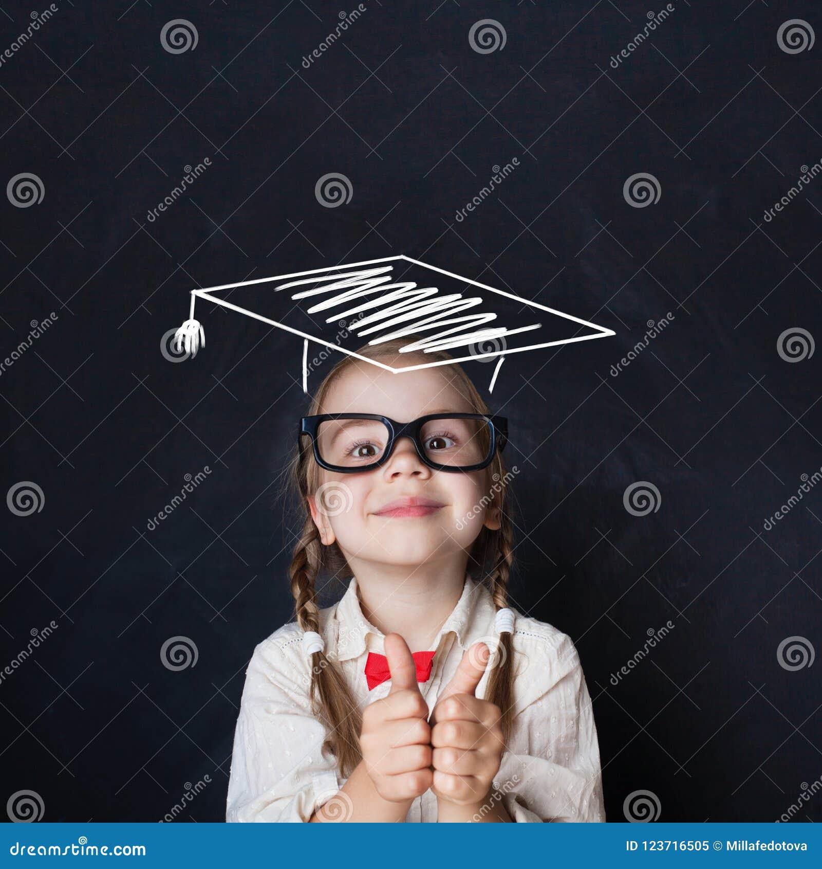 Pequeño niño del genio en sombrero de la graduación con el pulgar para arriba