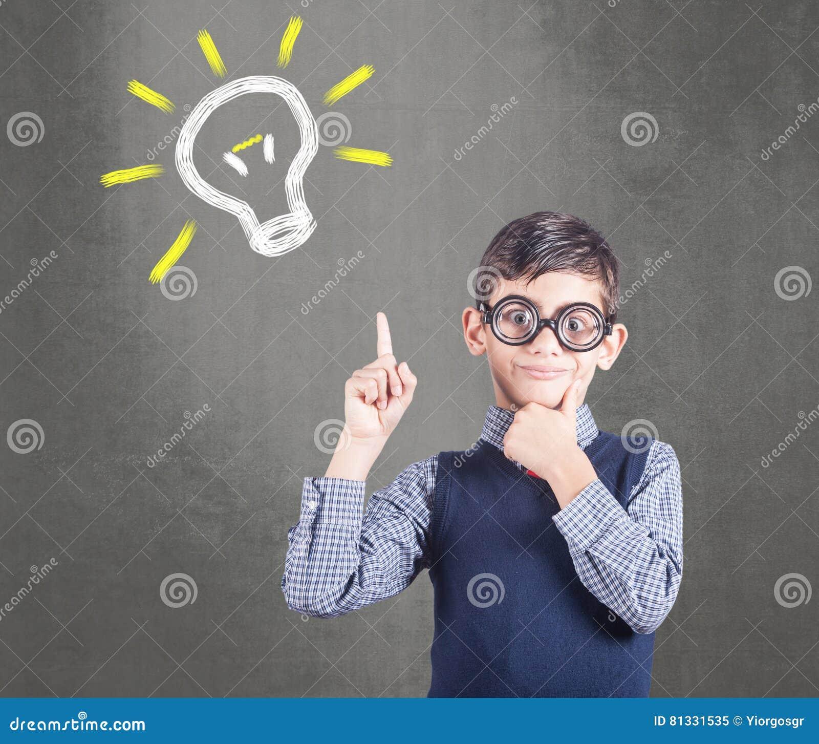 Pequeño niño divertido del genio que tiene una idea