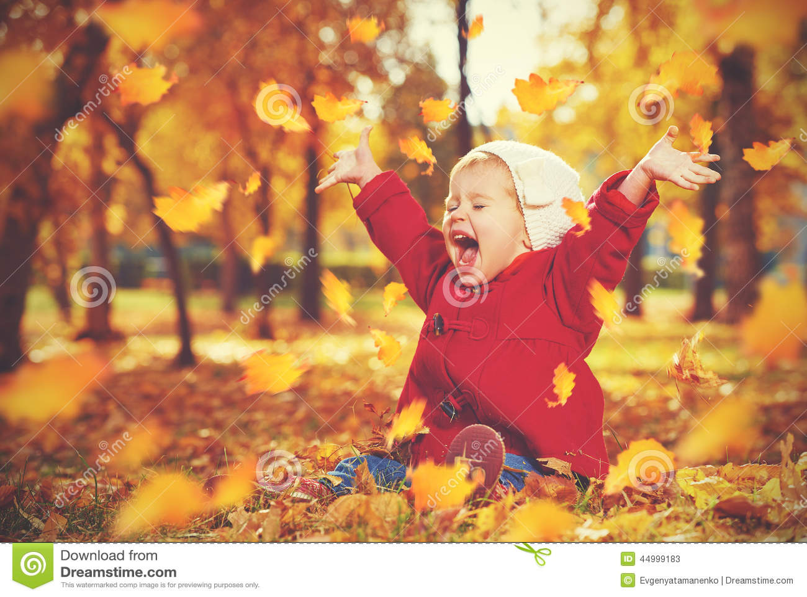 Pequeño niño feliz, bebé que ríe y que juega en otoño