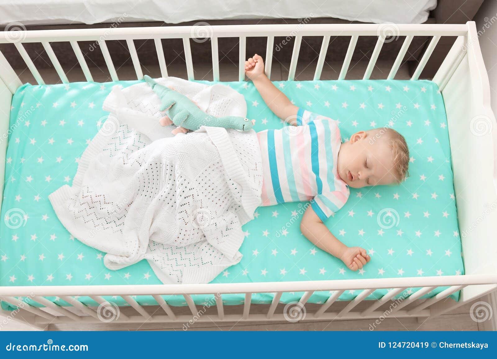 Pequeño niño lindo que duerme en pesebre