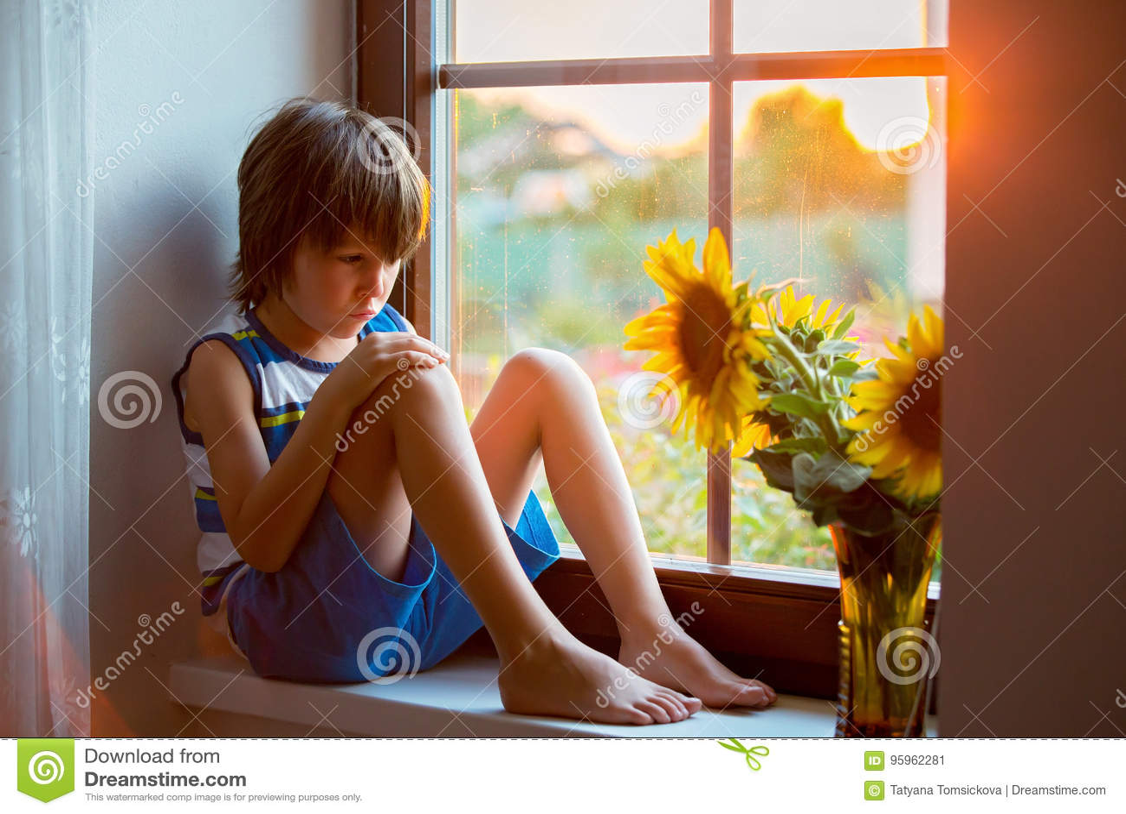 Pequeño niño lindo triste del niño, sentándose en una ventana, jugando con