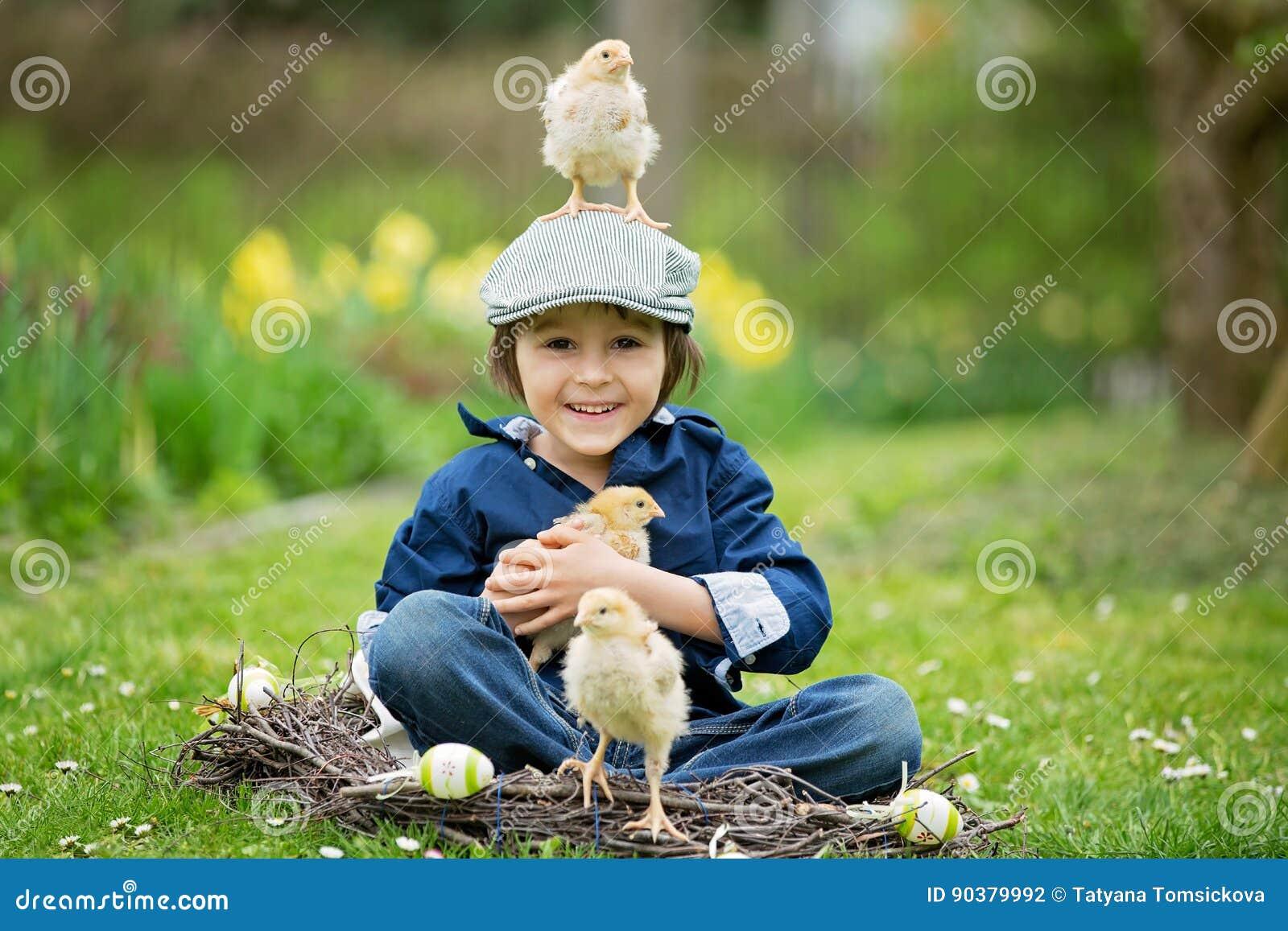 Pequeño niño preescolar lindo, muchacho, jugando con los huevos de Pascua y c