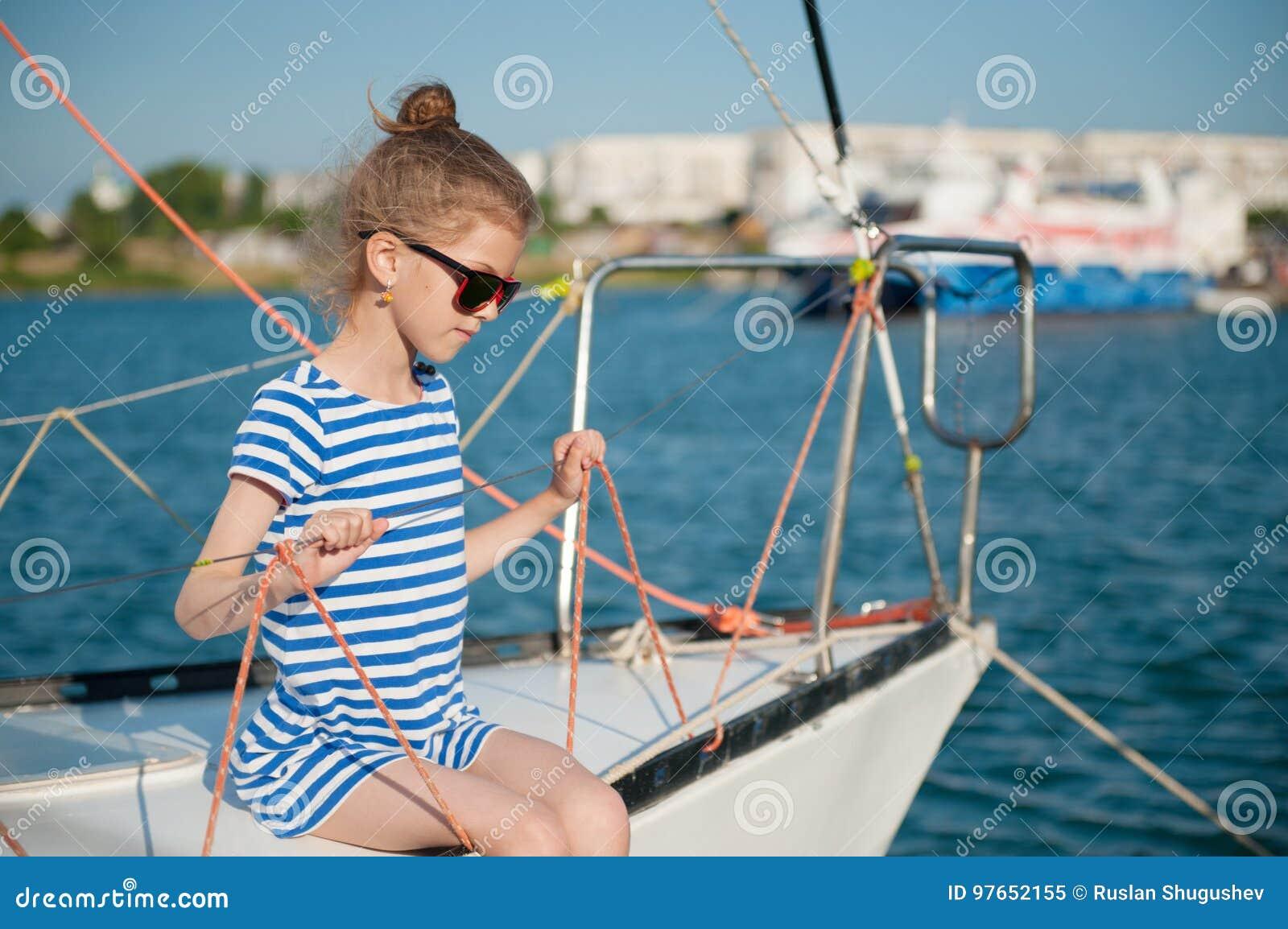 Pequeño niño sano lindo en las gafas de sol que se sientan a bordo del barco recreativo de lujo
