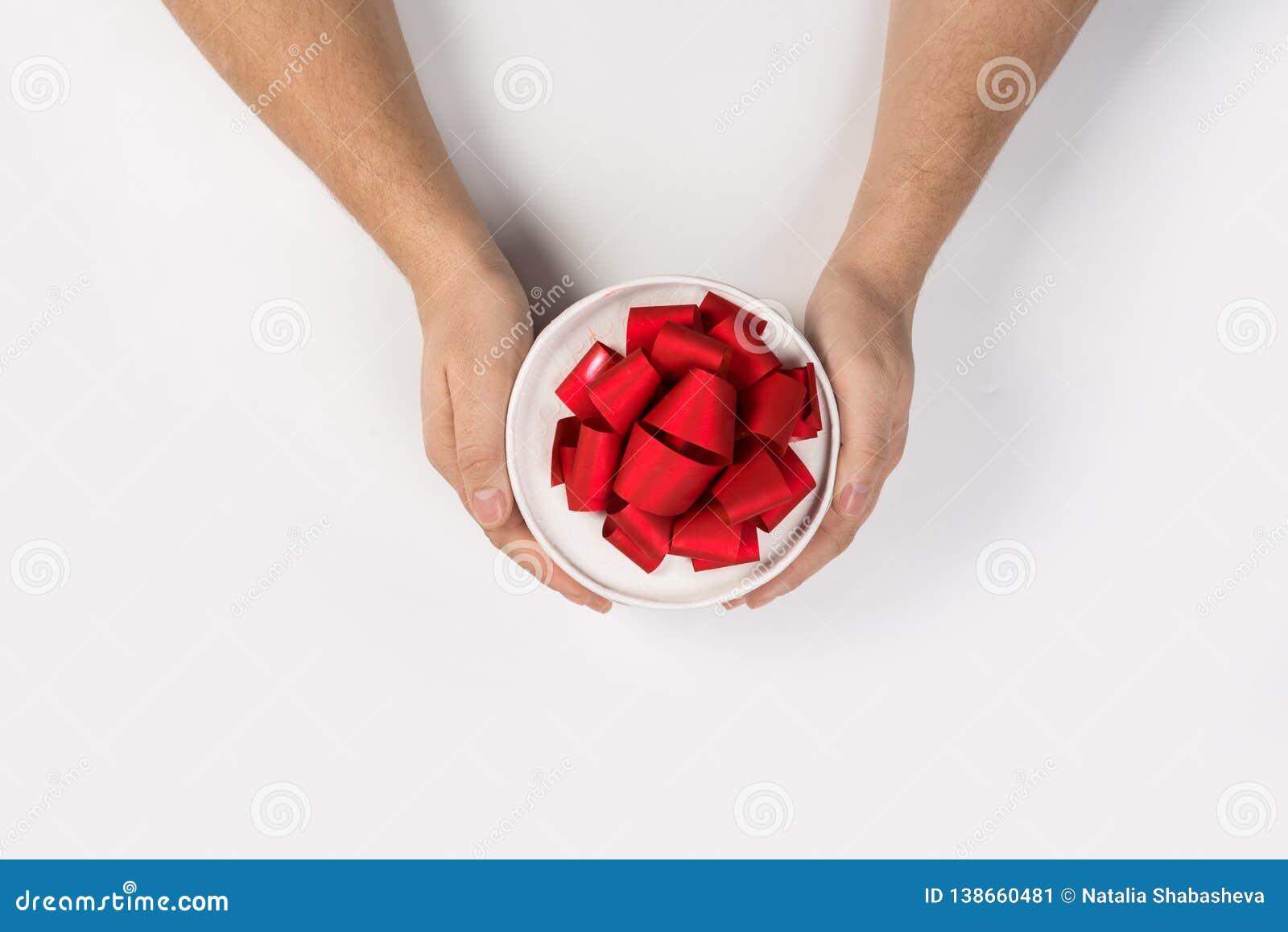 Pequeño presente con el arco rojo de la cinta en manos del hombre en el fondo blanco