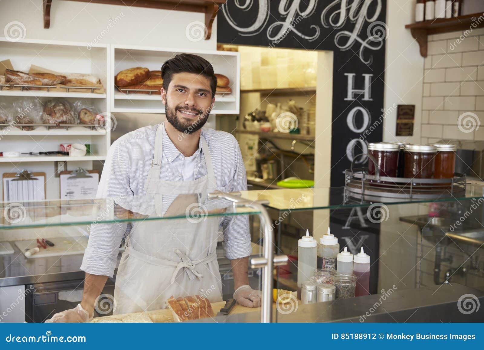 Pequeño propietario de negocio detrás del contador de una barra del bocadillo