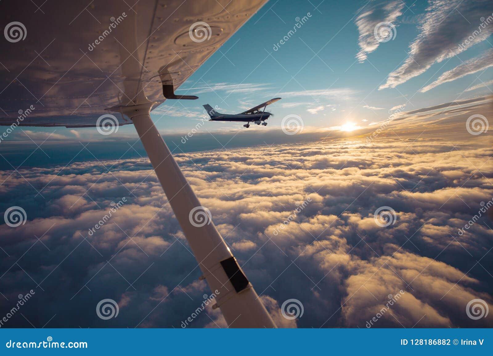 Pequeño vuelo del aeroplano del solo motor en el cielo magnífico de la puesta del sol a través del mar de nubes