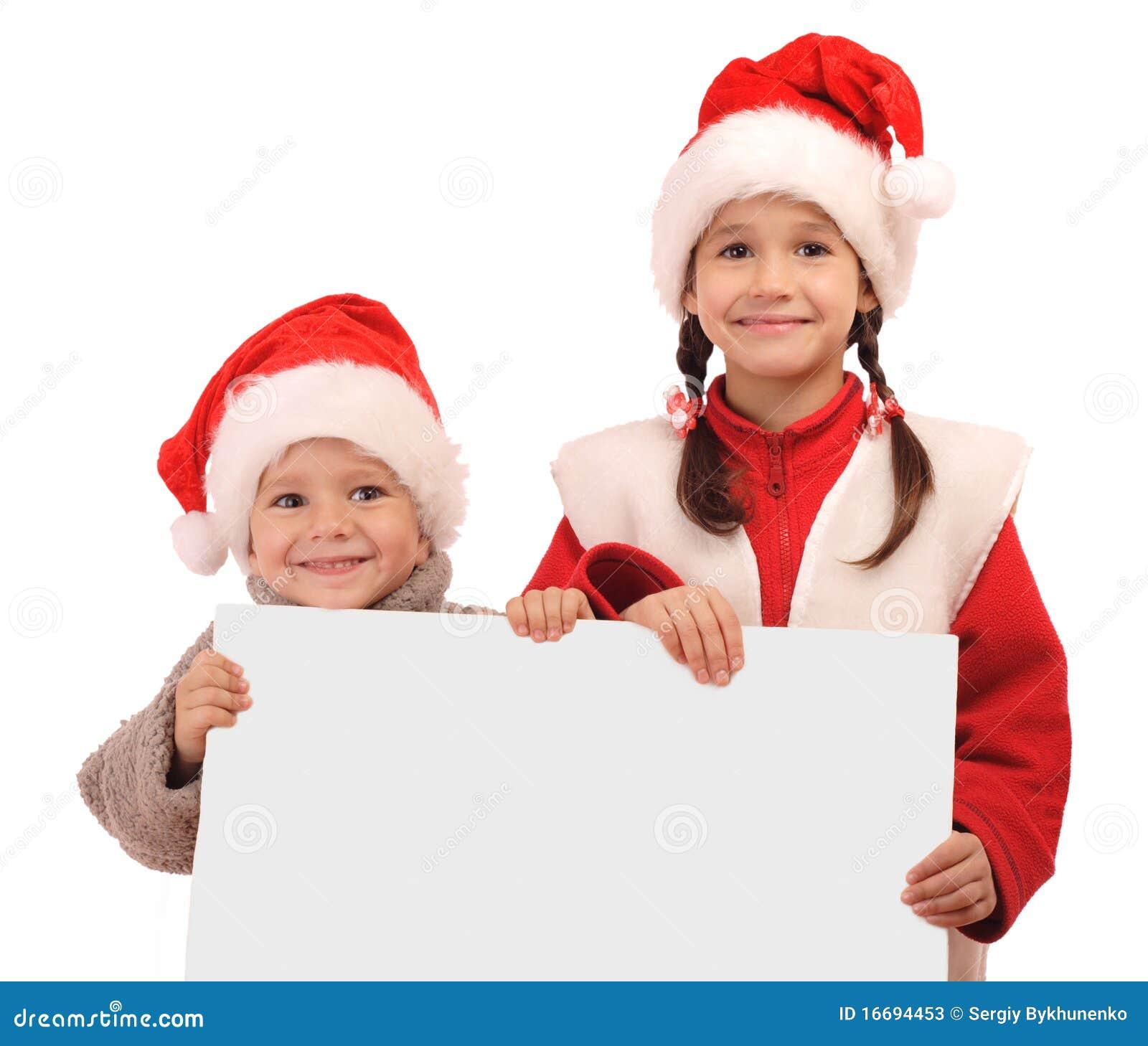 Pequeños niños en sombreros de la Navidad con la bandera