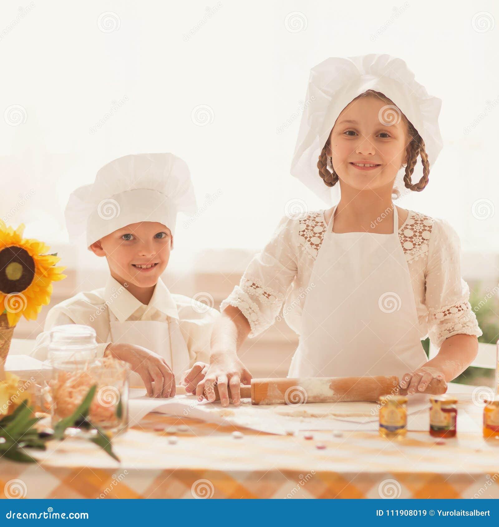 Pequeños Niños Felices Bajo La Forma De Cocinero Para Cocinar La Comida  Deliciosa