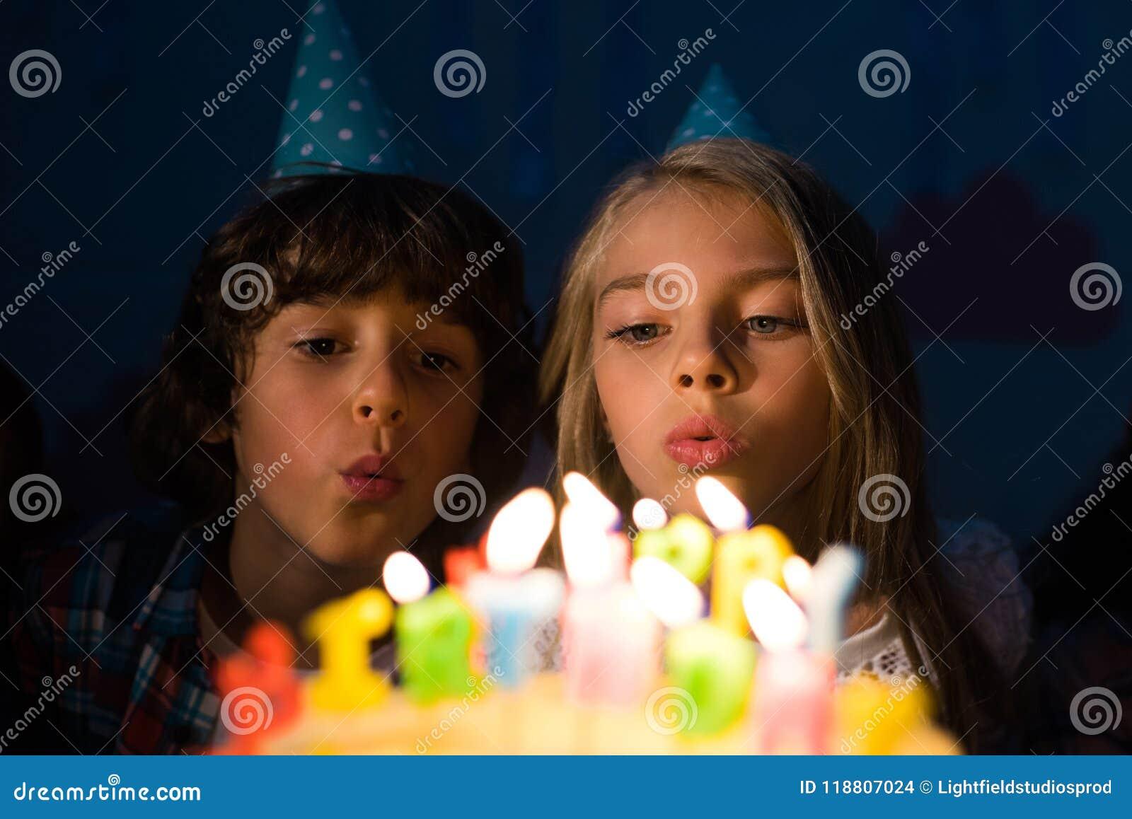 Pequeños niños lindos en los sombreros del partido que soplan velas