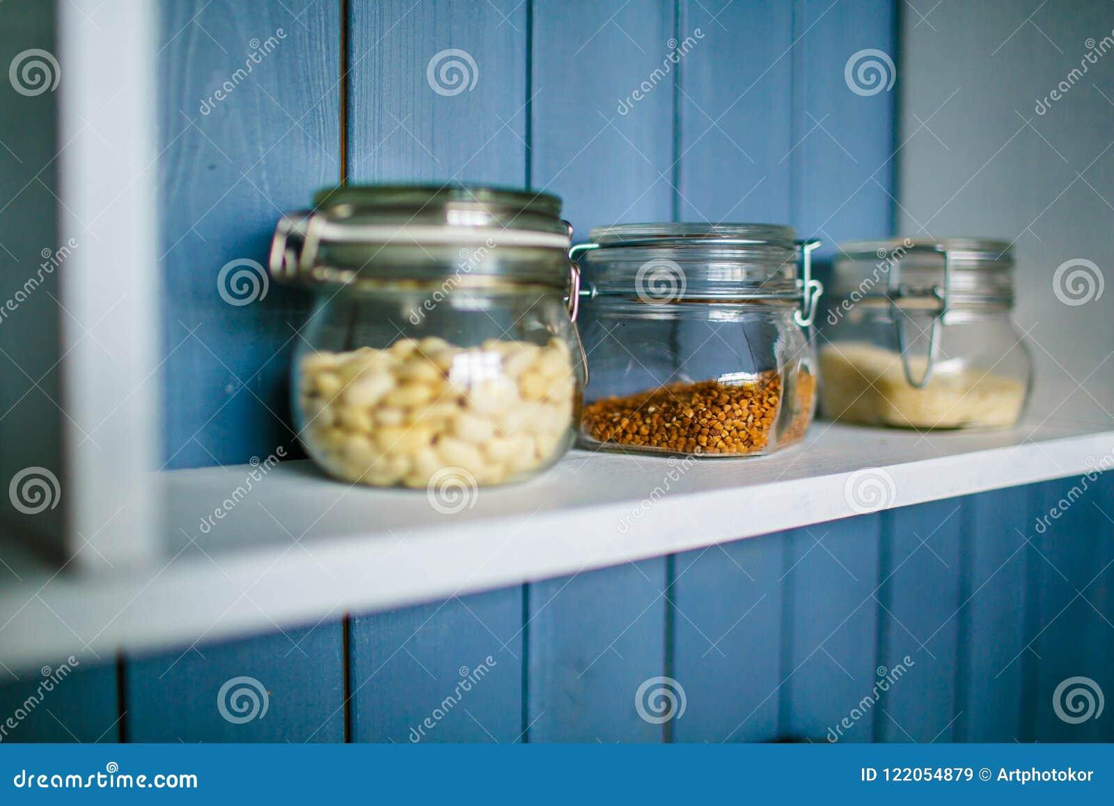 Pequeños tarros transparentes para la comida en estante de madera