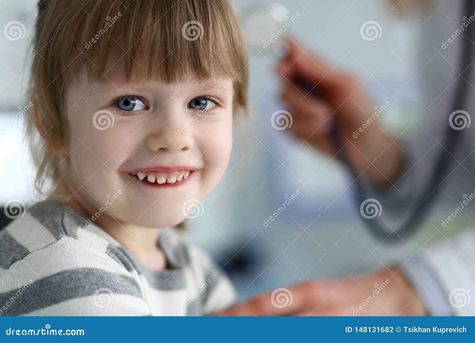 Peque?o paciente lindo sonriente que obra rec?procamente con el doctor de sexo femenino
