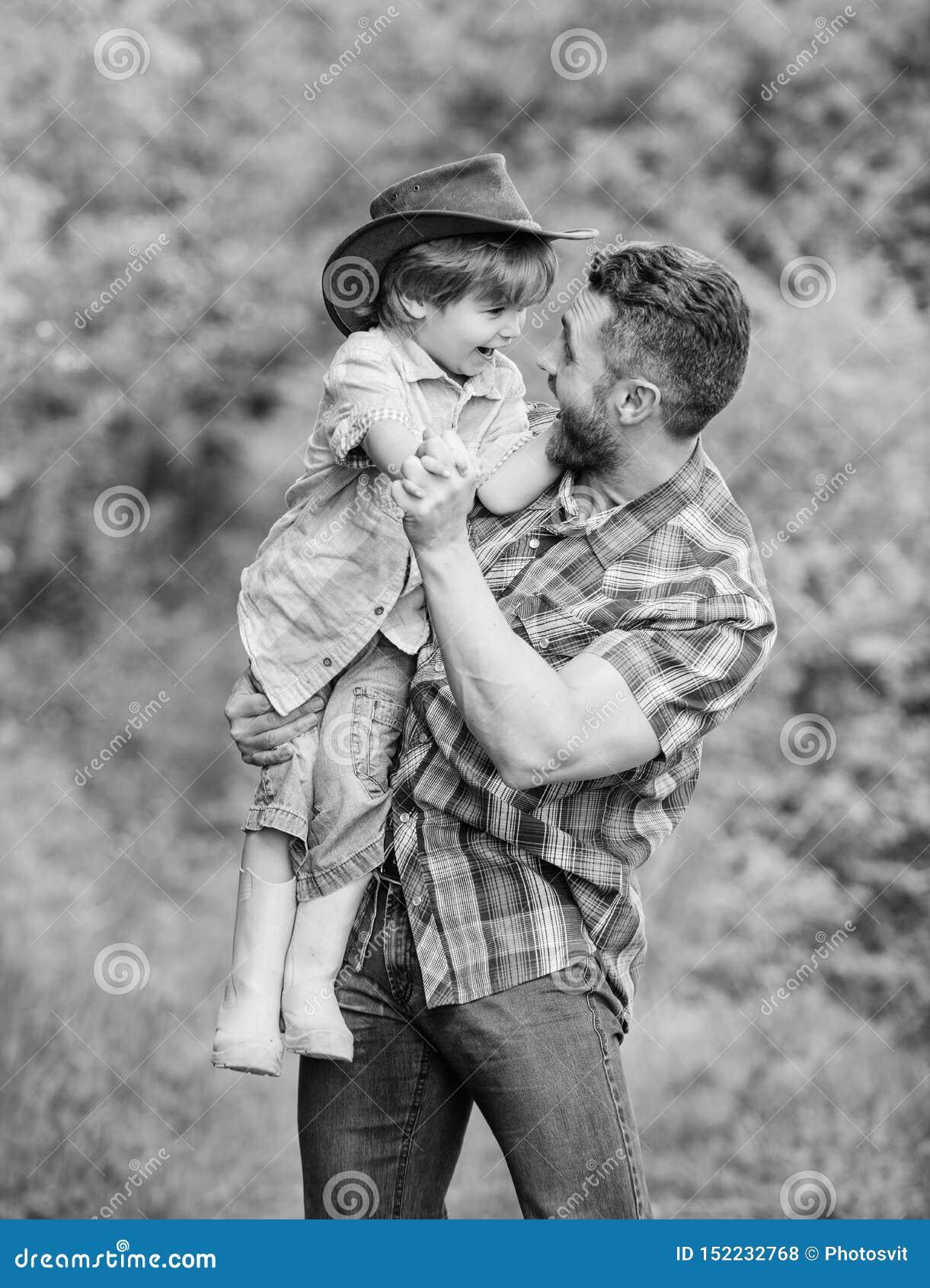 Peque?o padre de la ayuda del ni?o del muchacho en el cultivo padre e hijo en sombrero de vaquero en rancho ni?o en las botas de