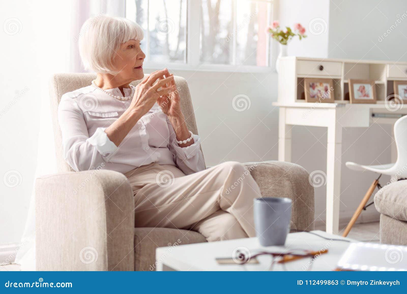 Pequeno senhora idosa que é profunda no pensamento em sua sala de visitas