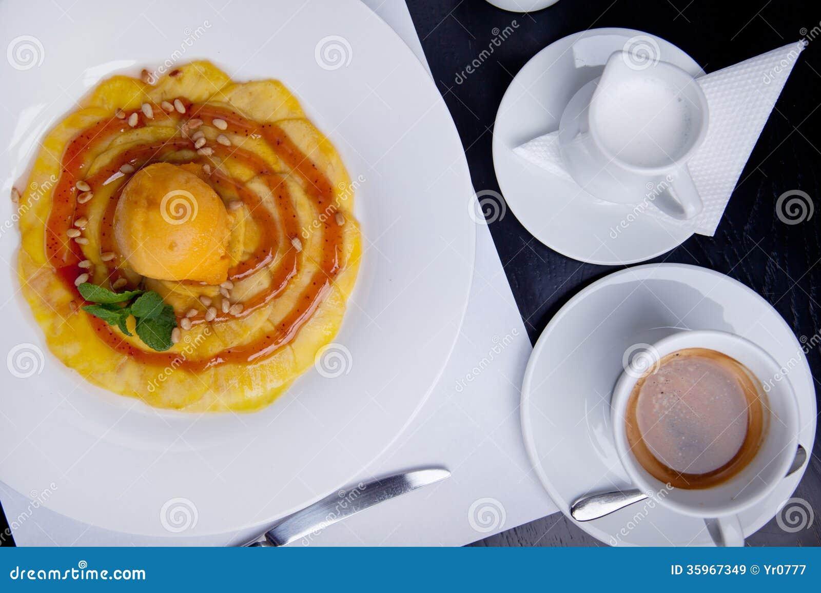 Pera cocida con la bola del helado y la taza del coffe