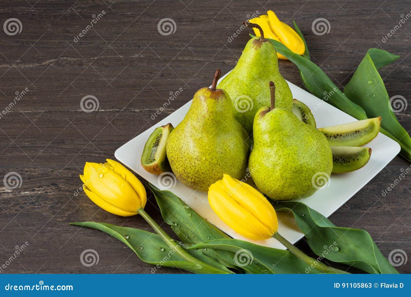 Pera verde, kiwi cortado y tulipanes amarillos en la placa blanca en el tablero de madera gris