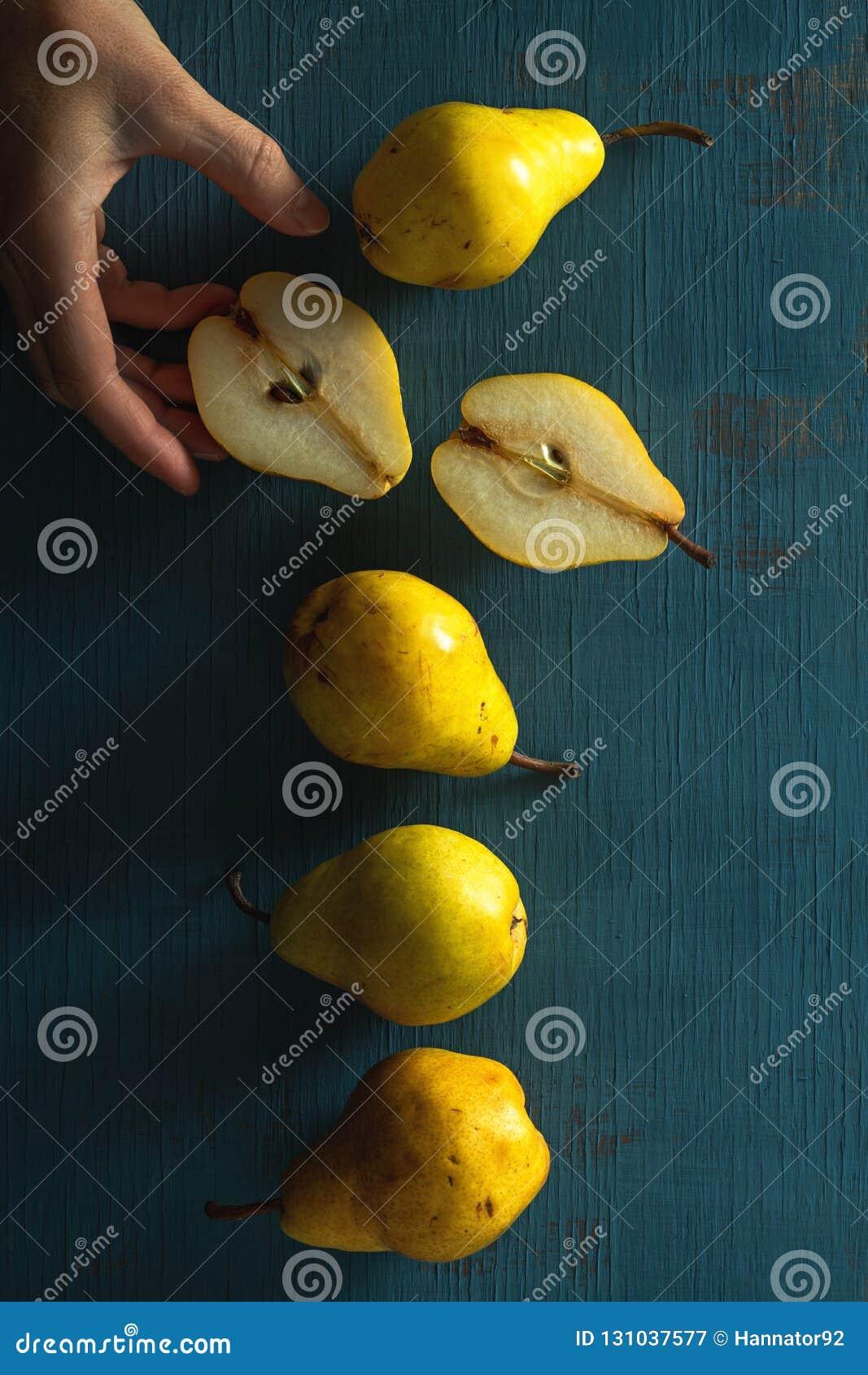 Peras amarelas em um fundo azul de madeira com mão da mulher