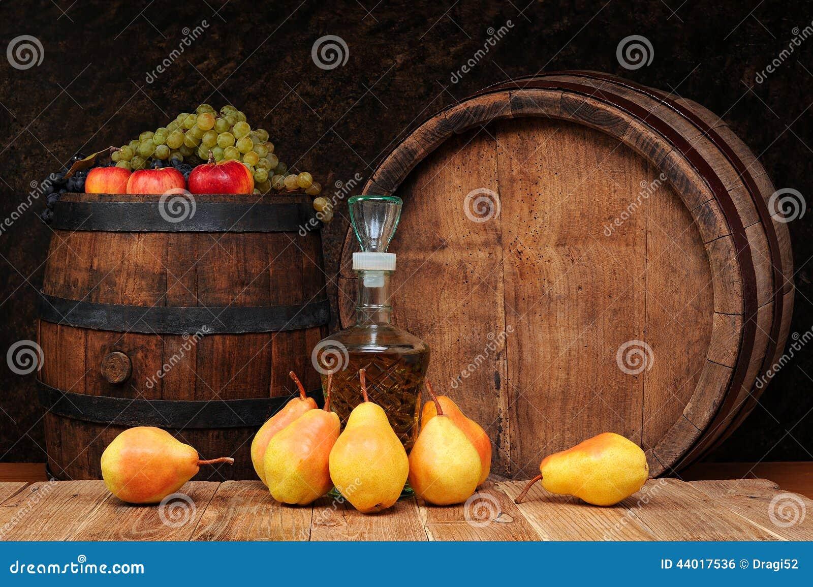 Peras, barril de madera y la botella del brandy