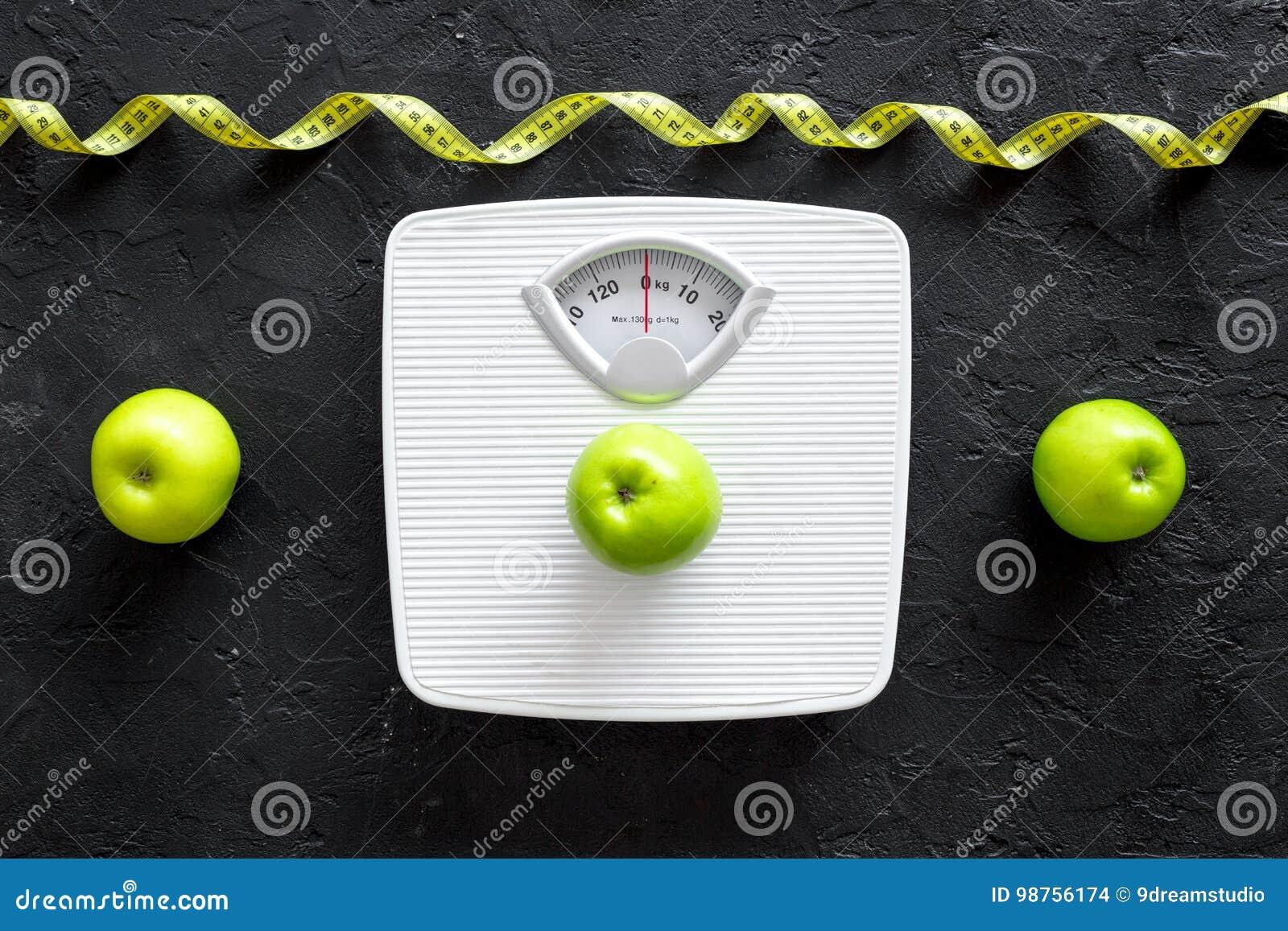 Perca o conceito do peso Escala de banheiro, fita de medição, maçãs na opinião superior do fundo preto